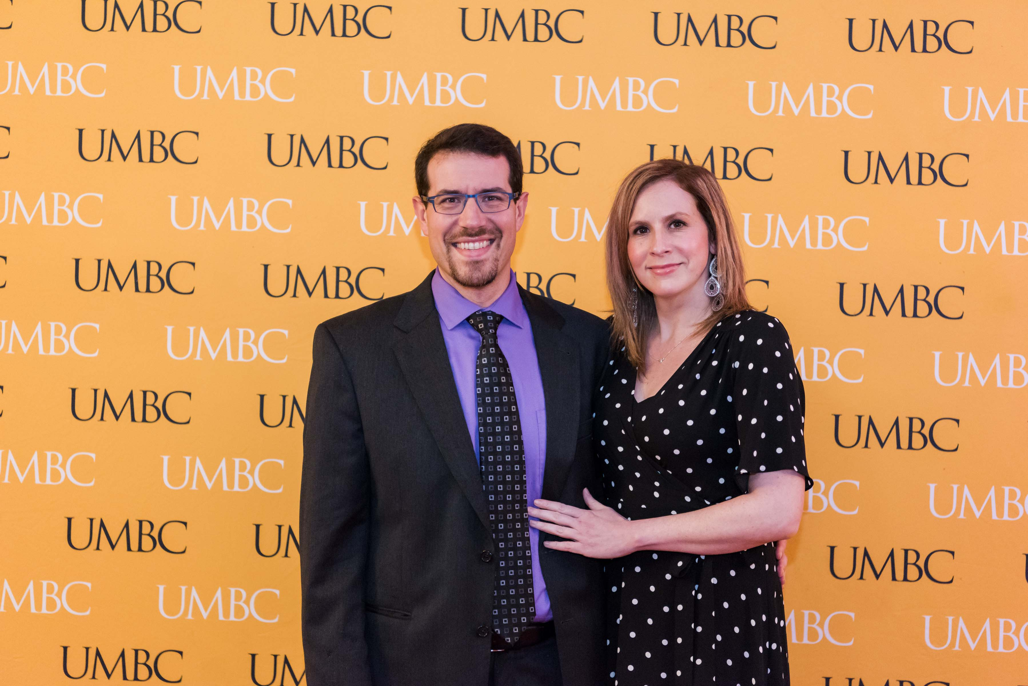 Man and woman pose together with UMBC wall for wine tasting
