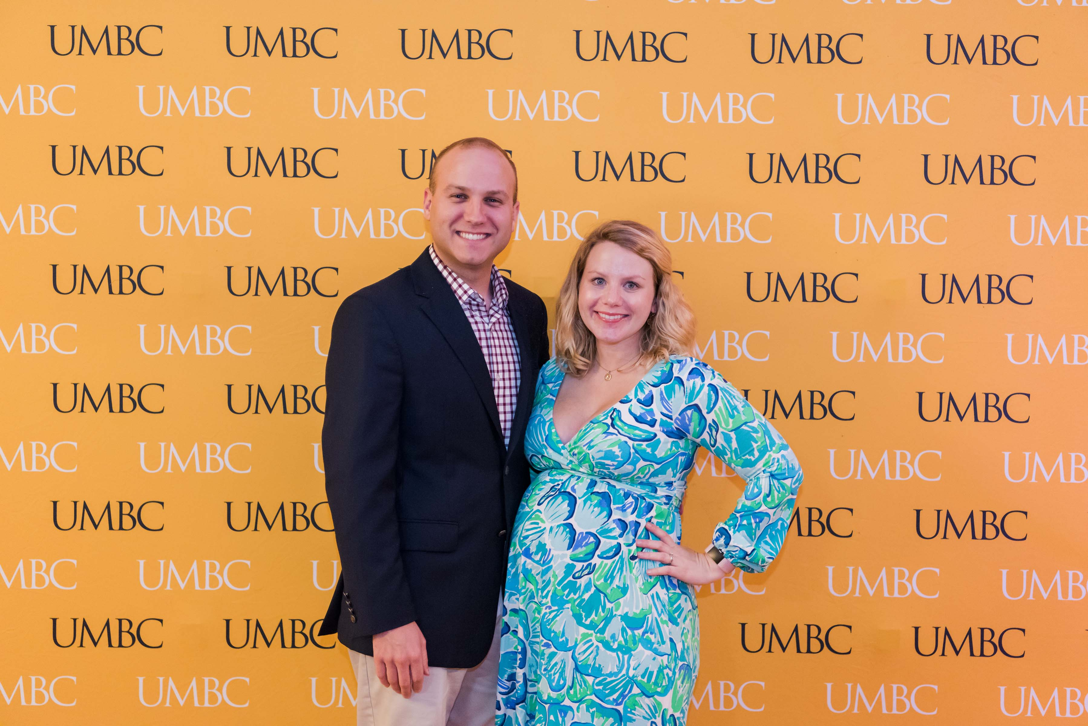 Man and pregnant woman pose in front of UMBC wall for CYA event