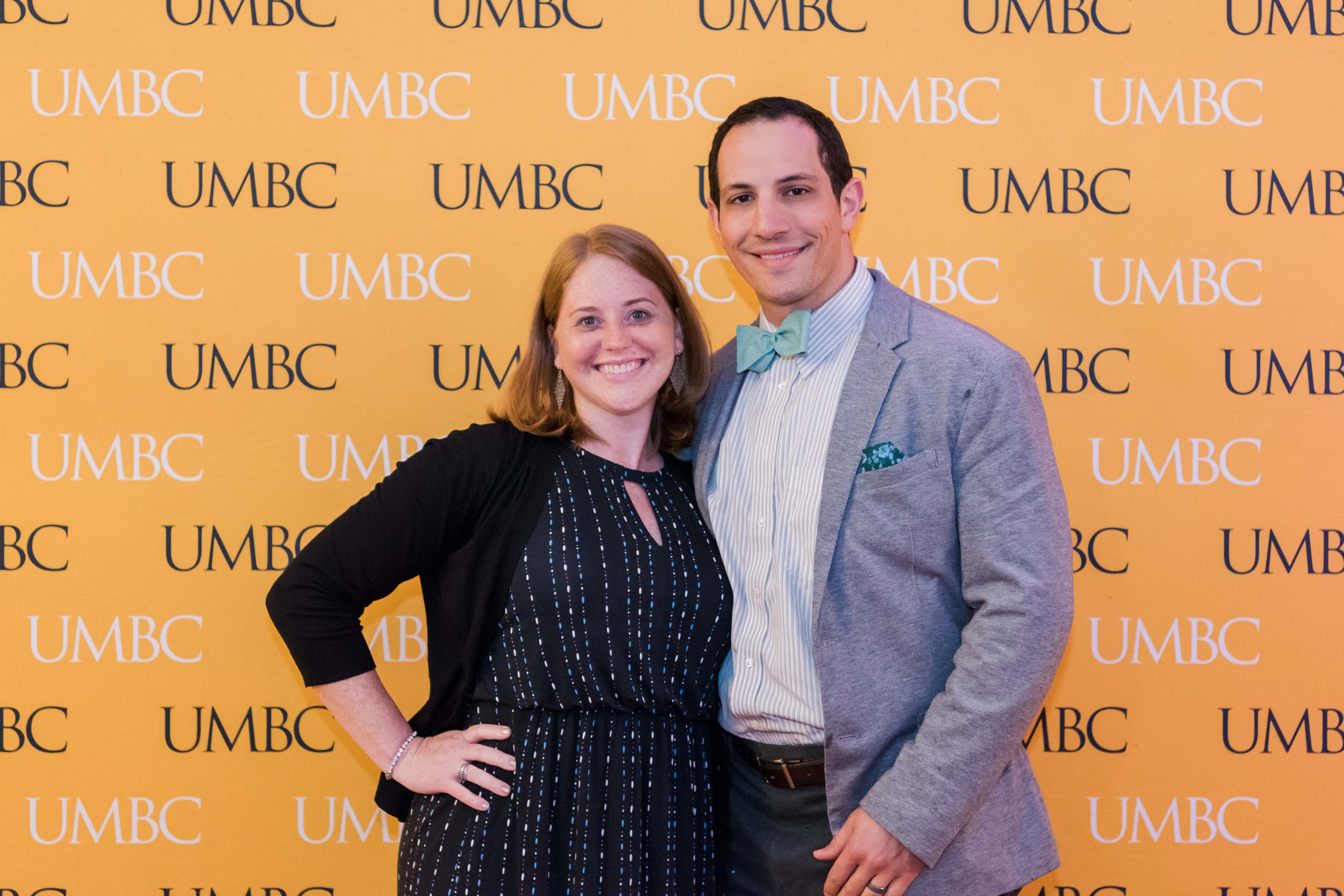 Man with bowtie poses with woman and UMBC wall for CYA wine tasting event