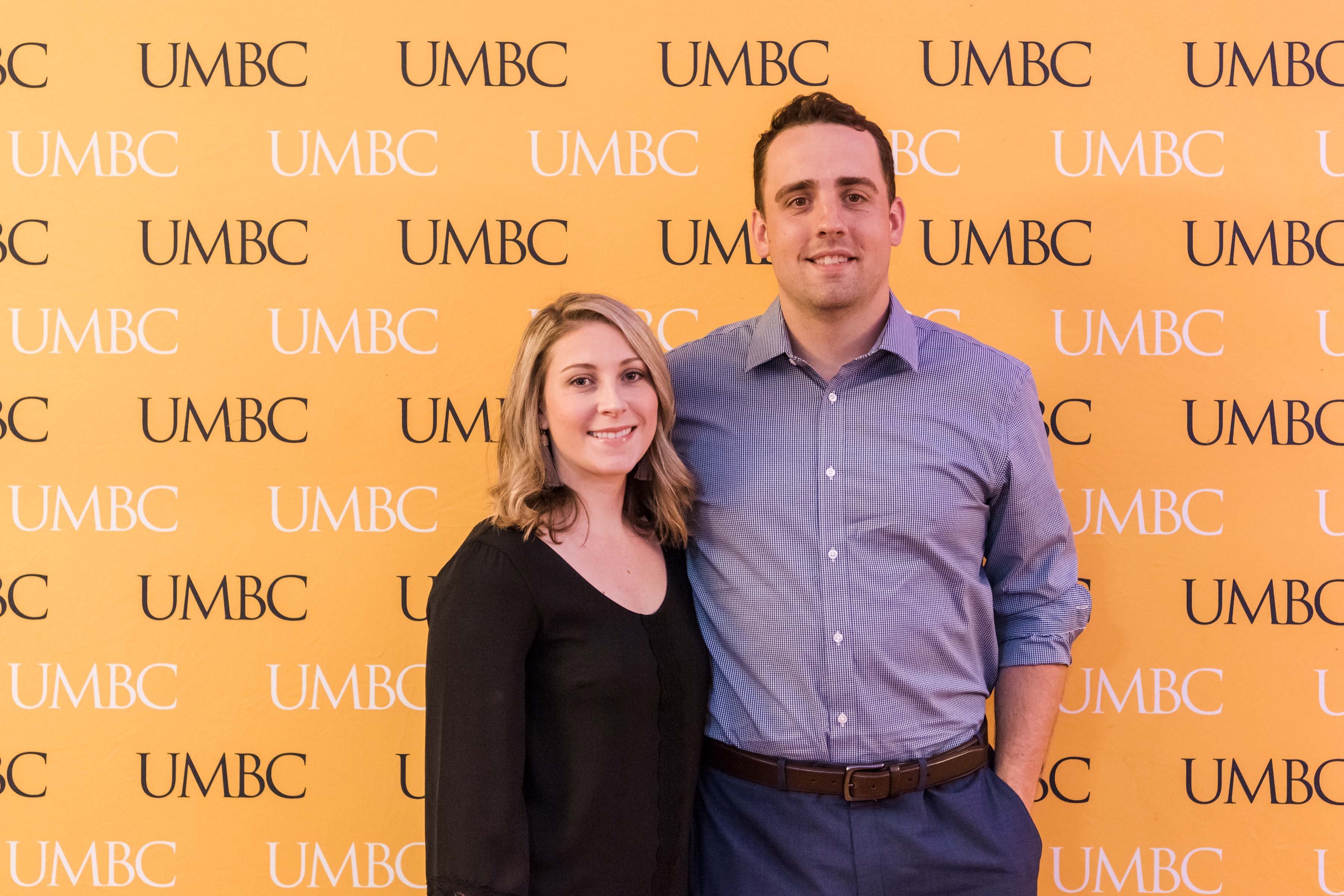 Man and woman pose with UMBC wall for wine tasting event