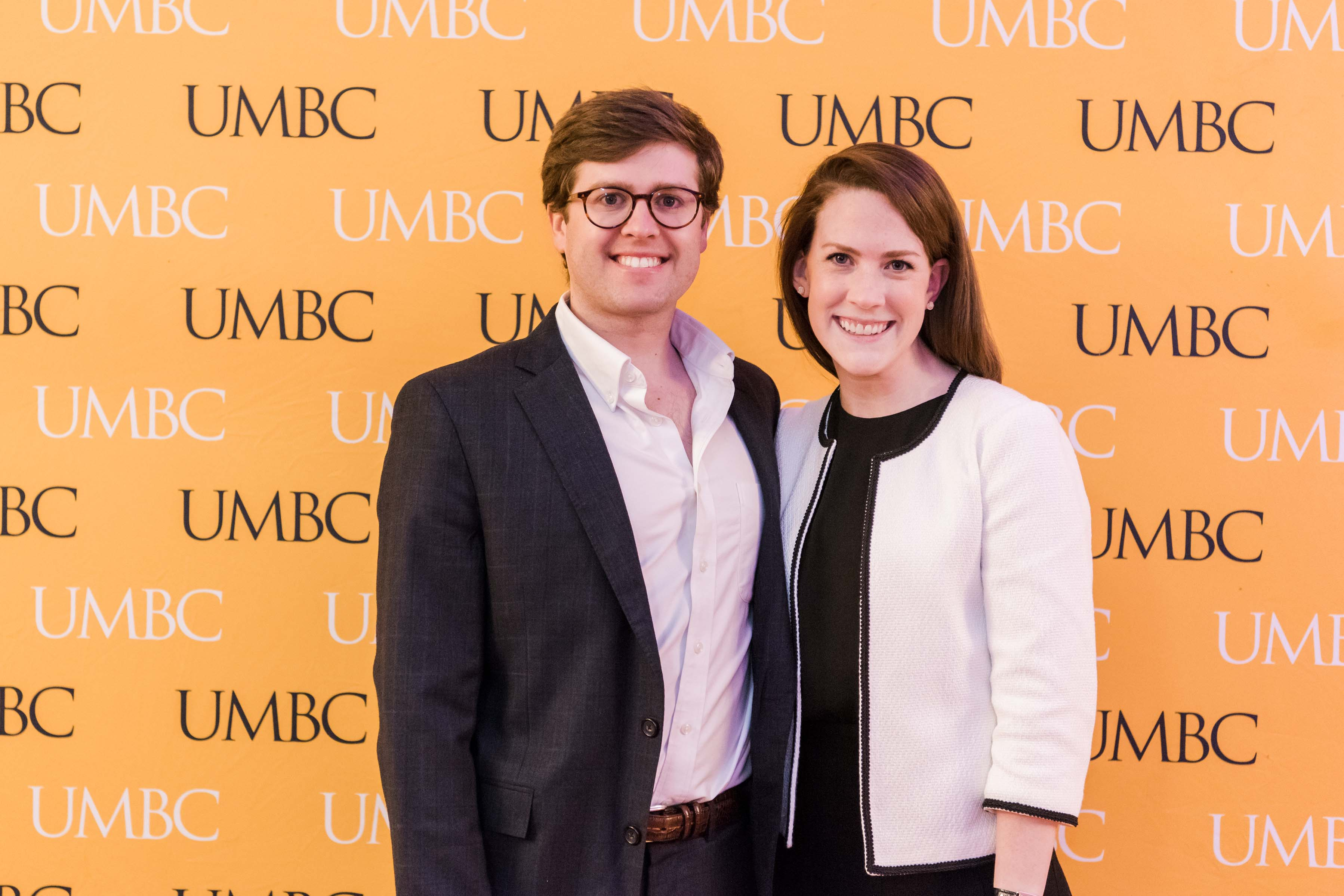 Man and woman pose for wine tasting event in front of UMBC wall