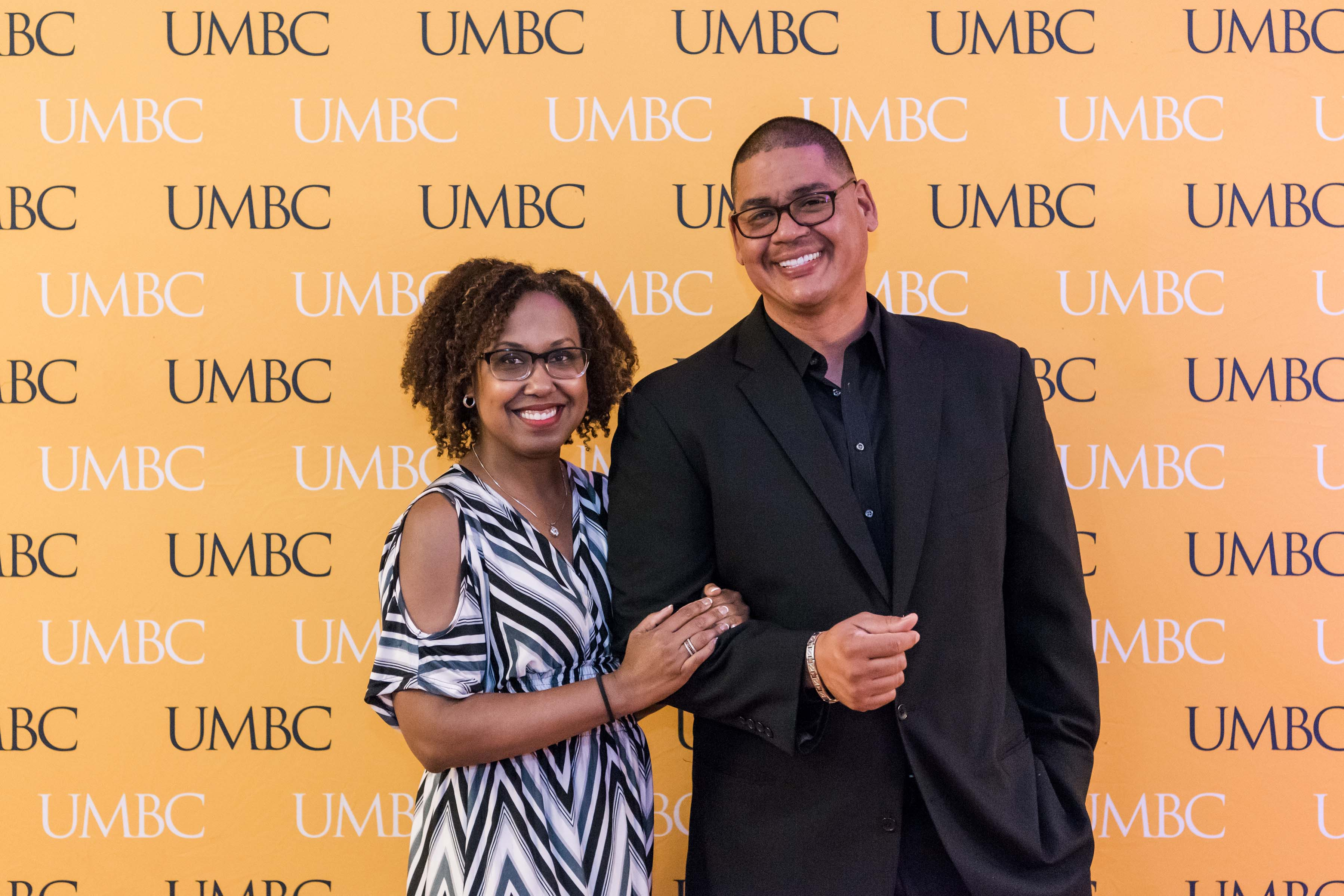 Couple pose with UMBC wall at 2018 CYA event