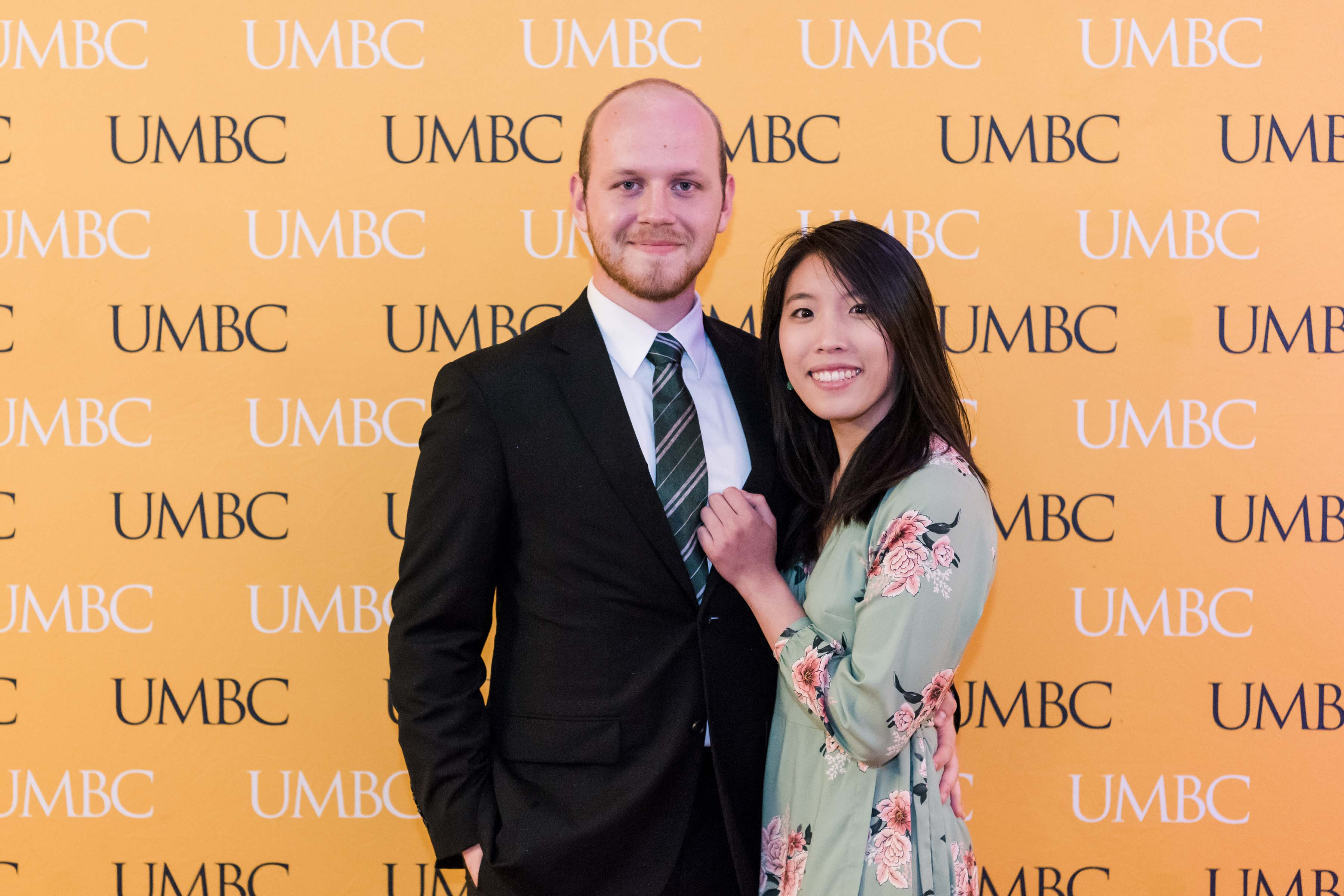 Couple pose at UMBC wall for CYA wine tasting event