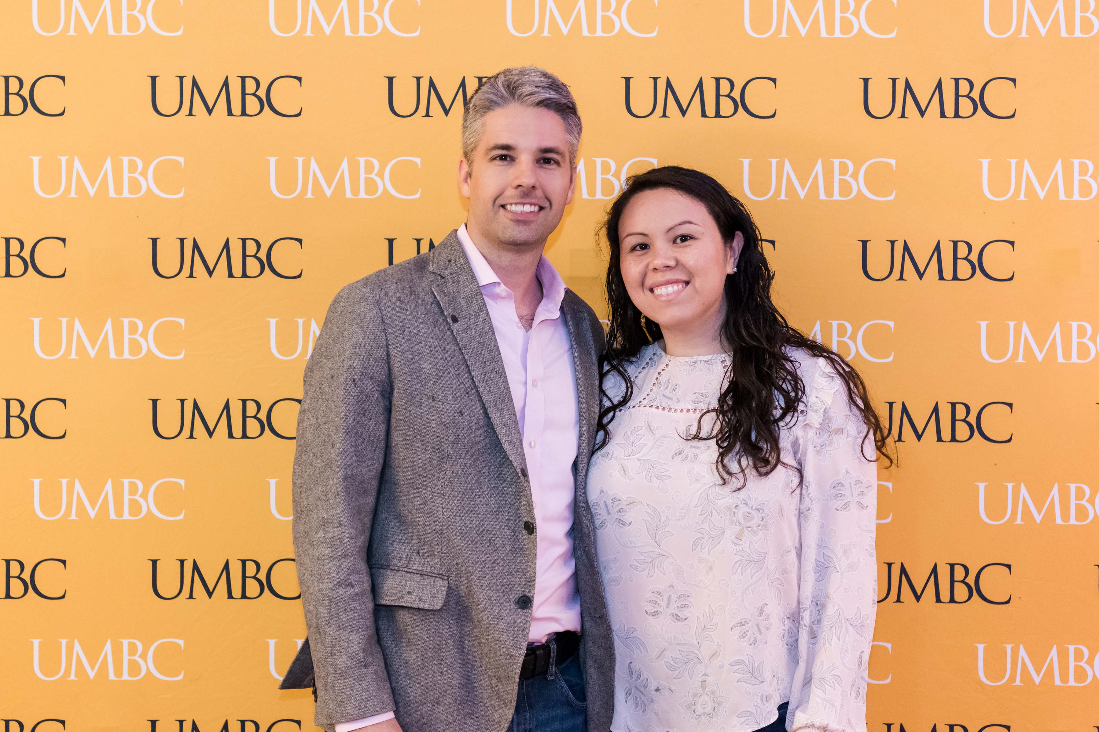 Guy and girl pose at UMBC wall for wine tasting