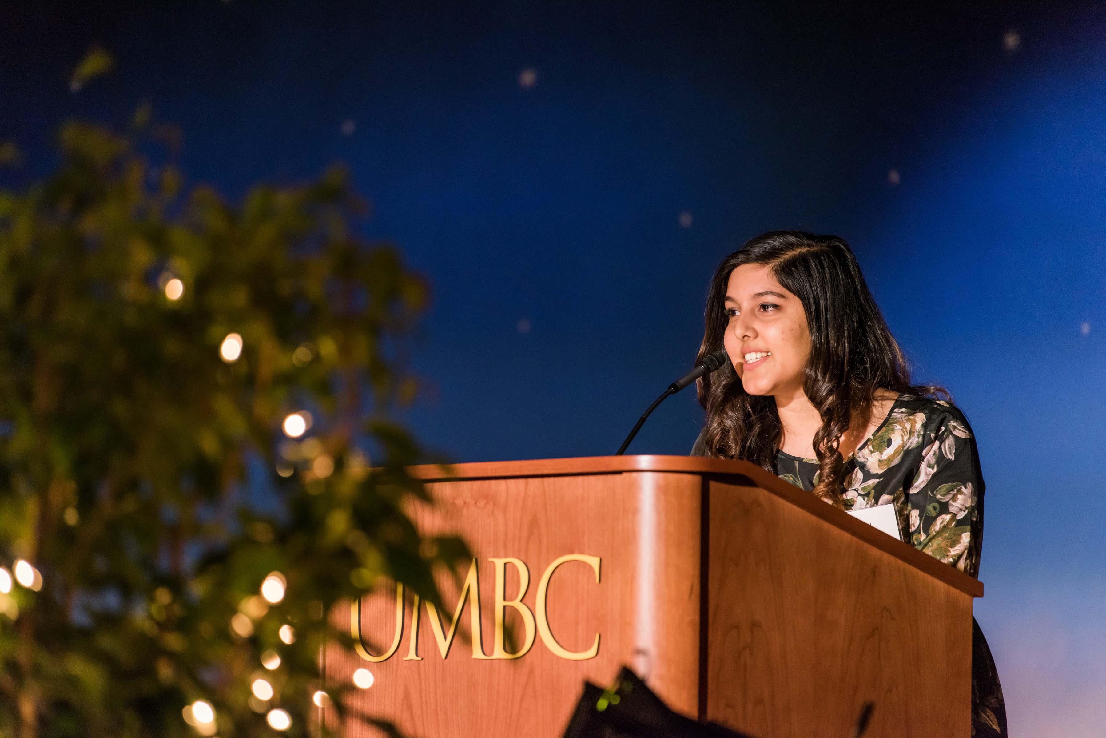 Poulomi Banerjee gives talk behind UMBC podium at 2018 wine tasting