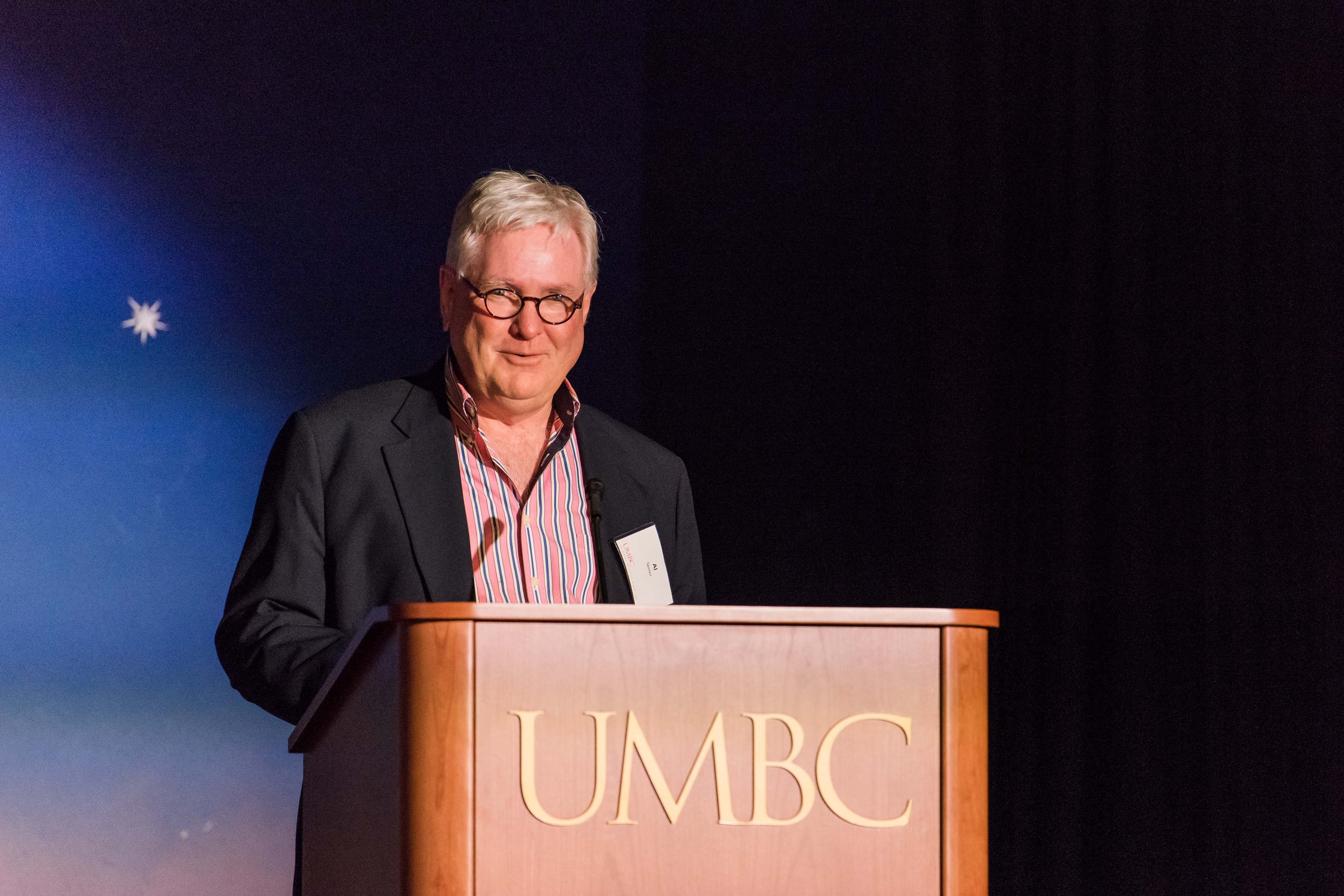 Al Spoler gives talk behind UMBC podium at wine tasting event