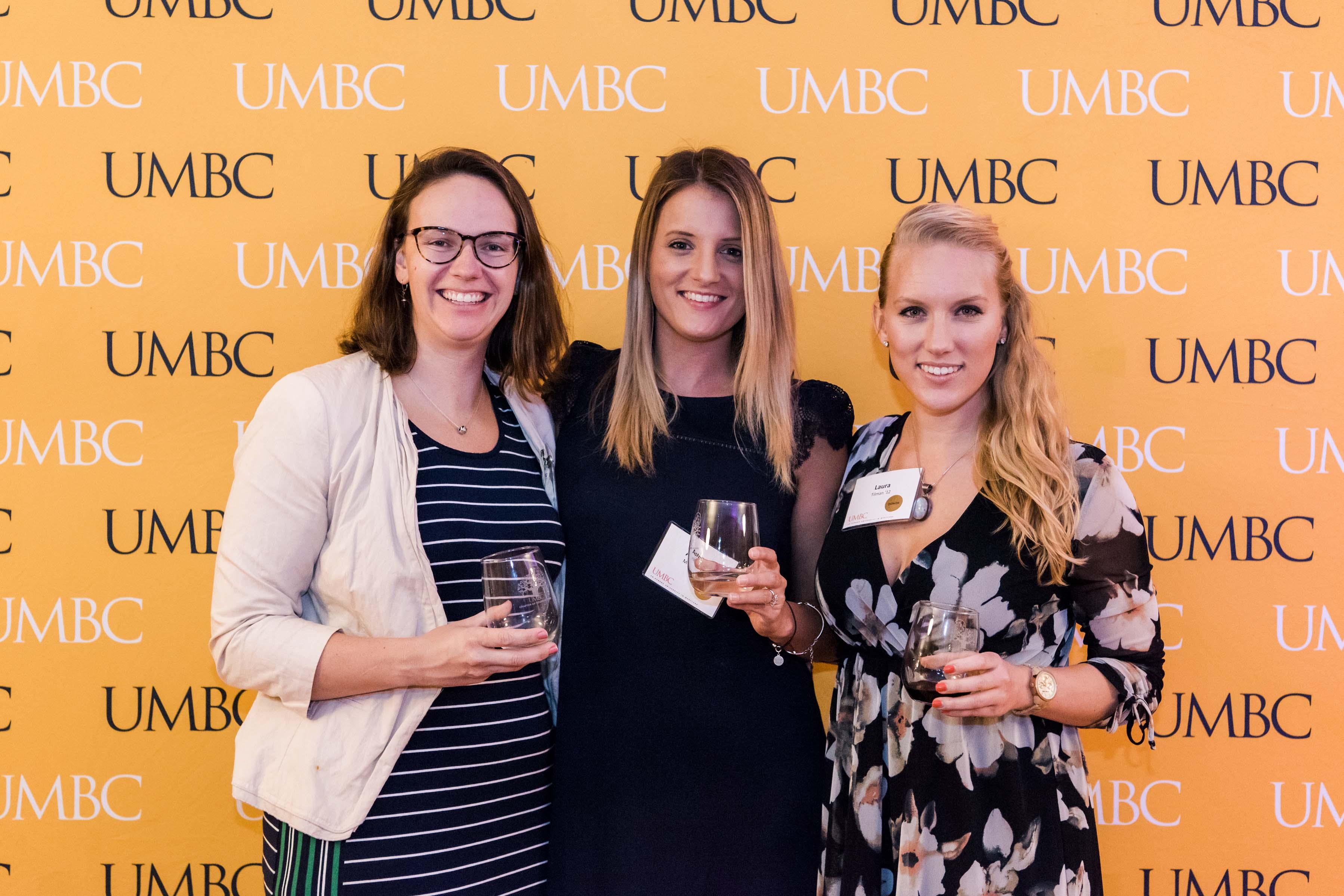 Three women pose with wine glasses at UMBC wall at 2018 wine tasting