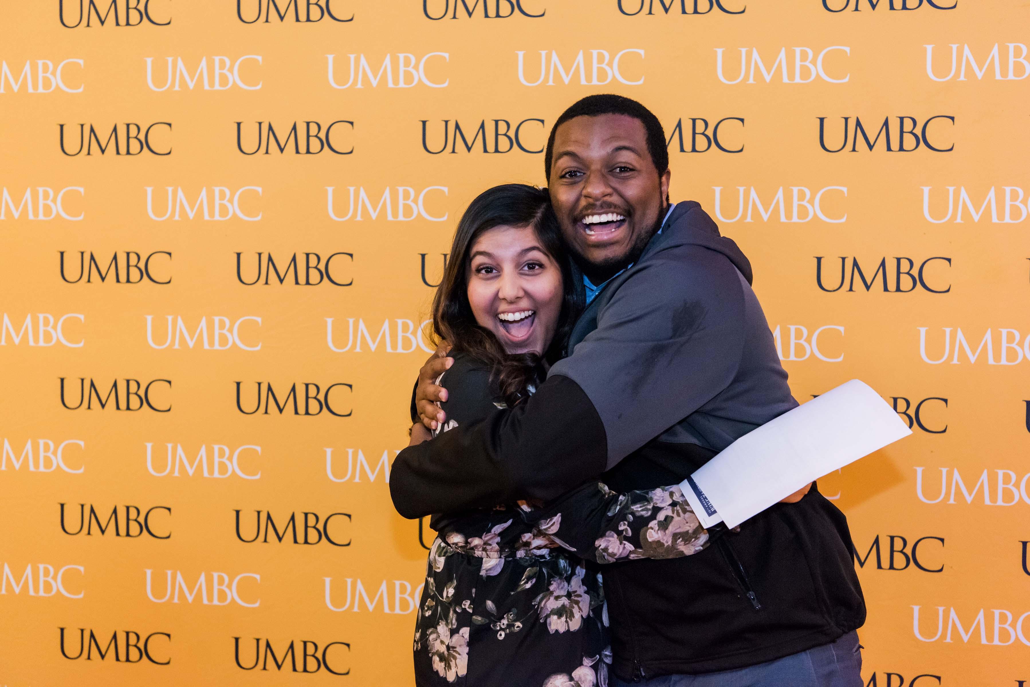 Two people hug at UMBC Wall at 2018 wine tasting