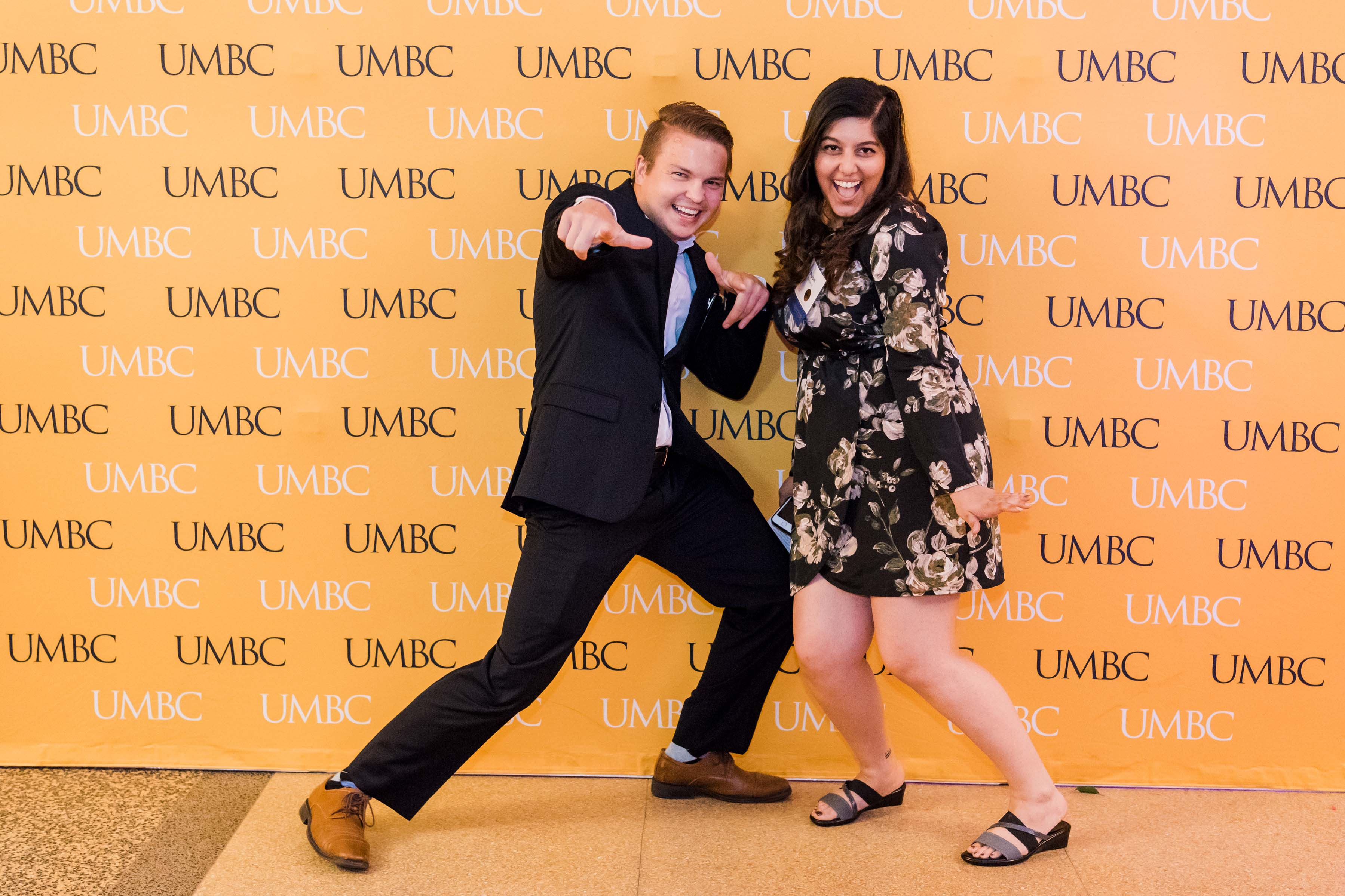 Two people do silly pose with UMBC wall at CYA wine tasting
