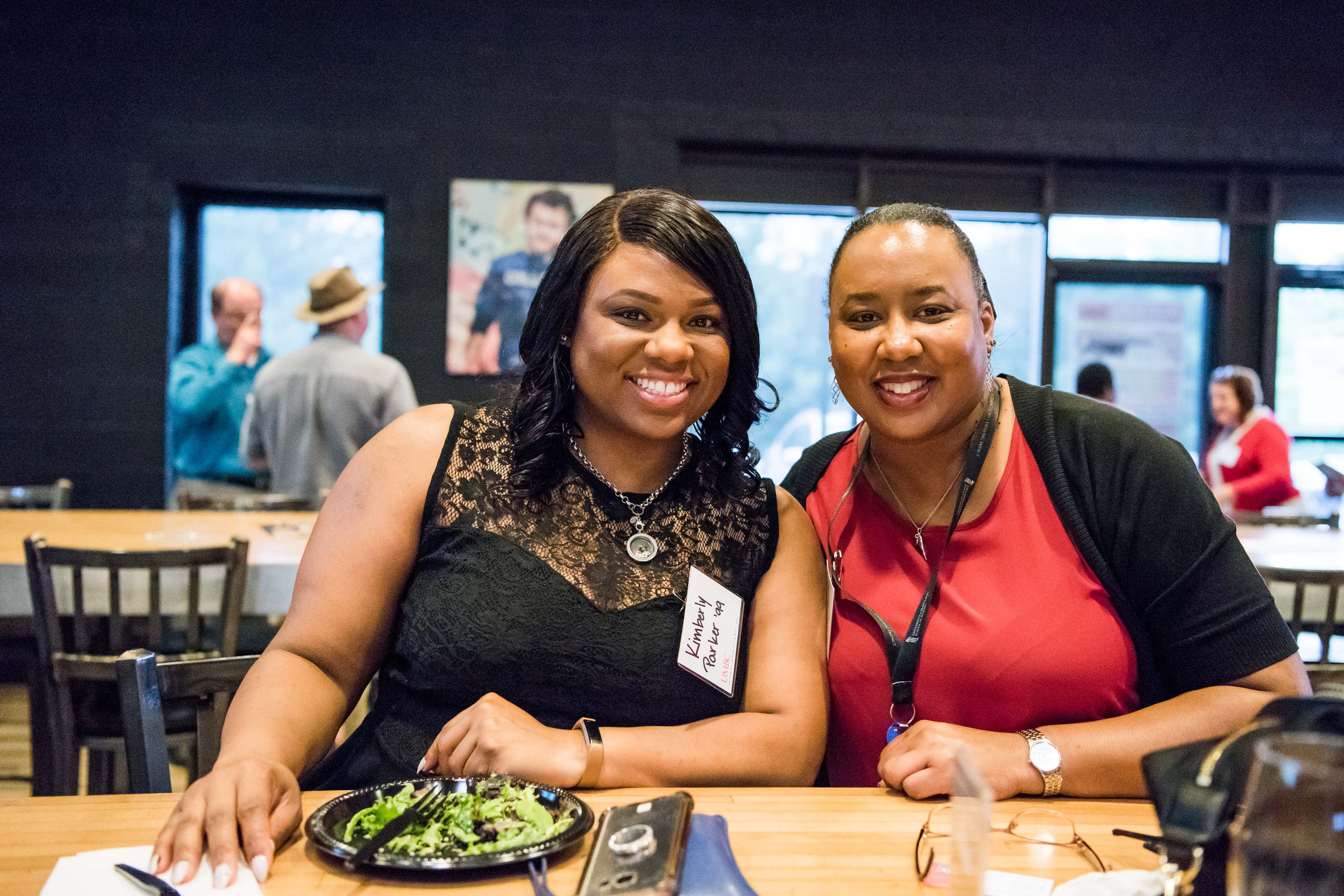 Two Women sit at table together at Jailbreak happy hour