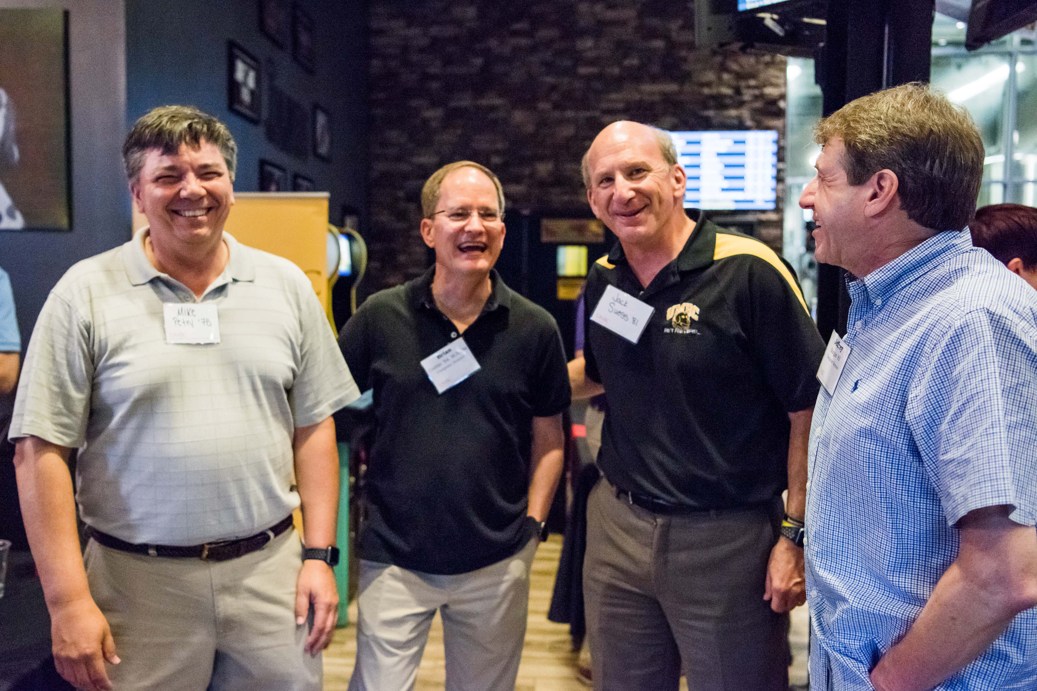 Group of men laughing together at Jailbreak happy hour