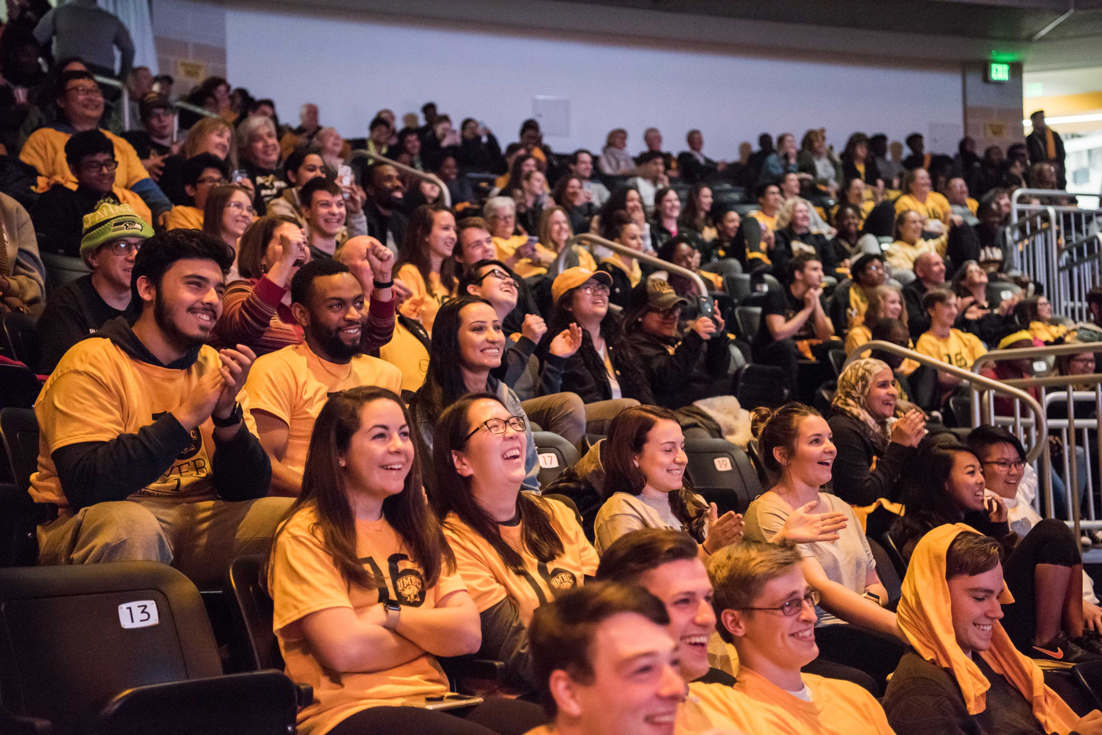 Crowd with UMBC shirts clap at Mens basketball celebration