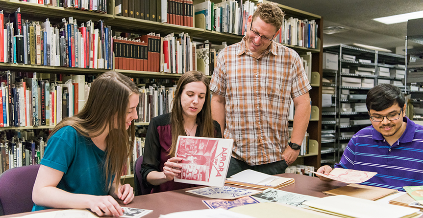People hover around table in special collections