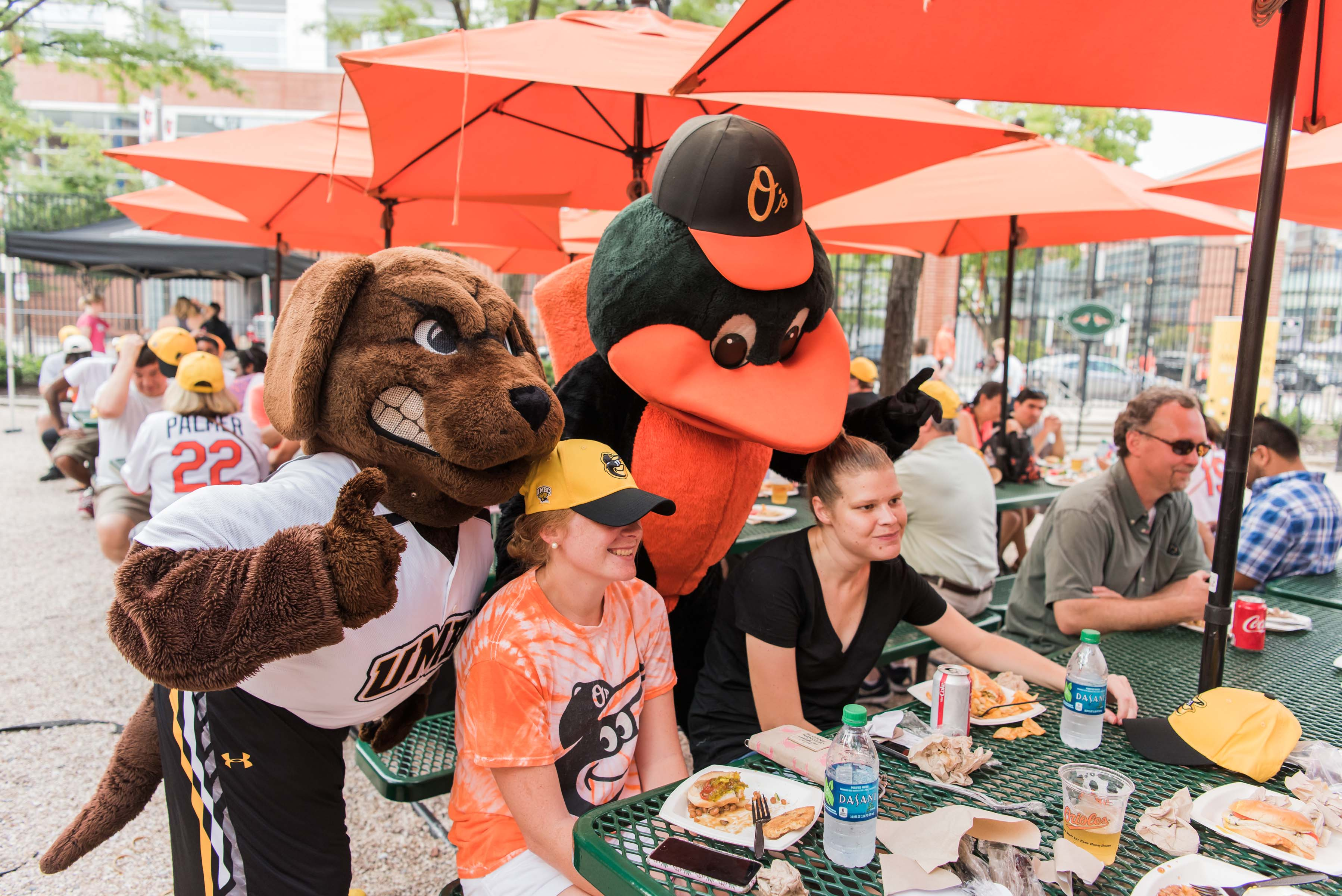 Orioles and UMBC mascot posing with fans at table