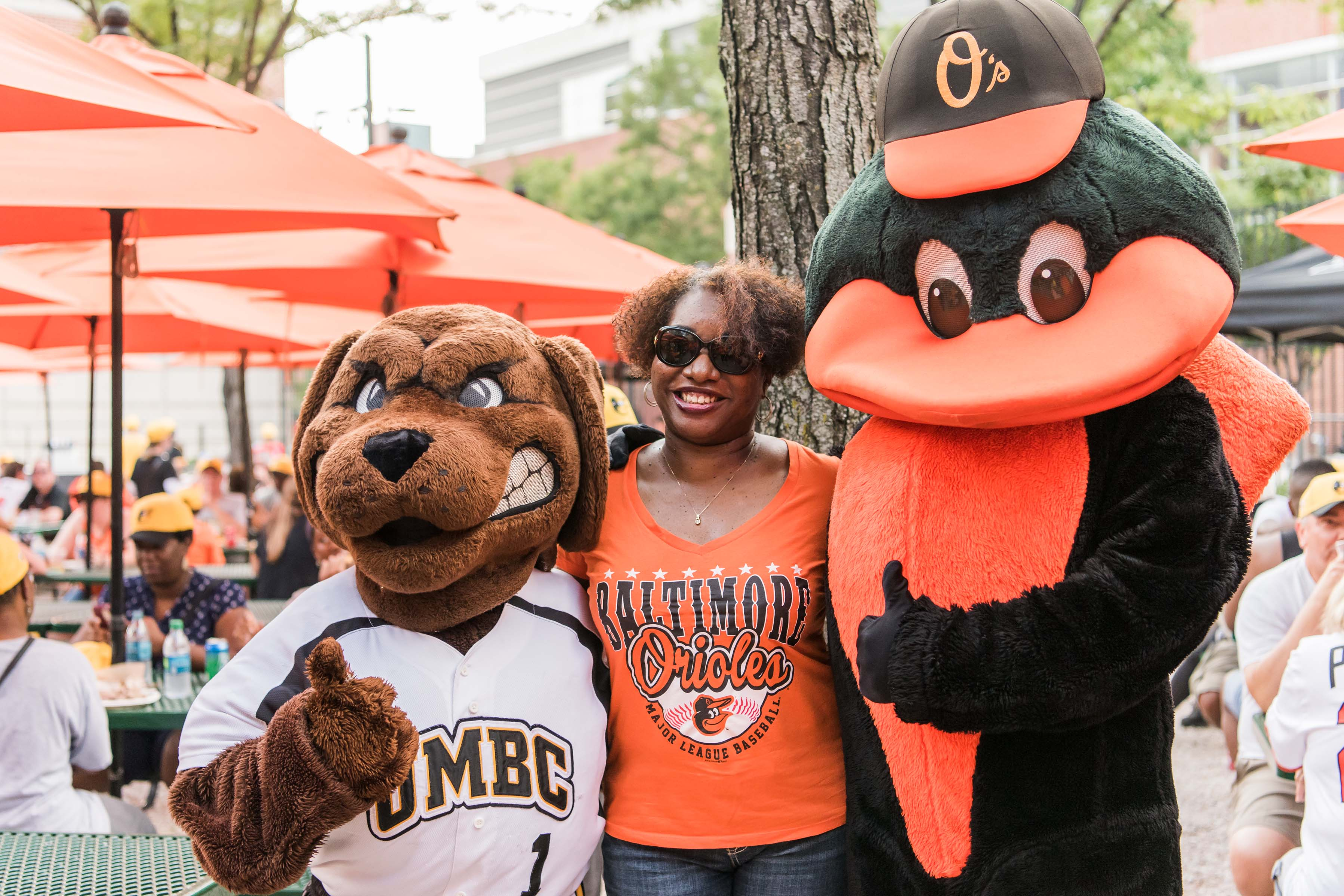 Orioles and UMBC mascot posing with fan
