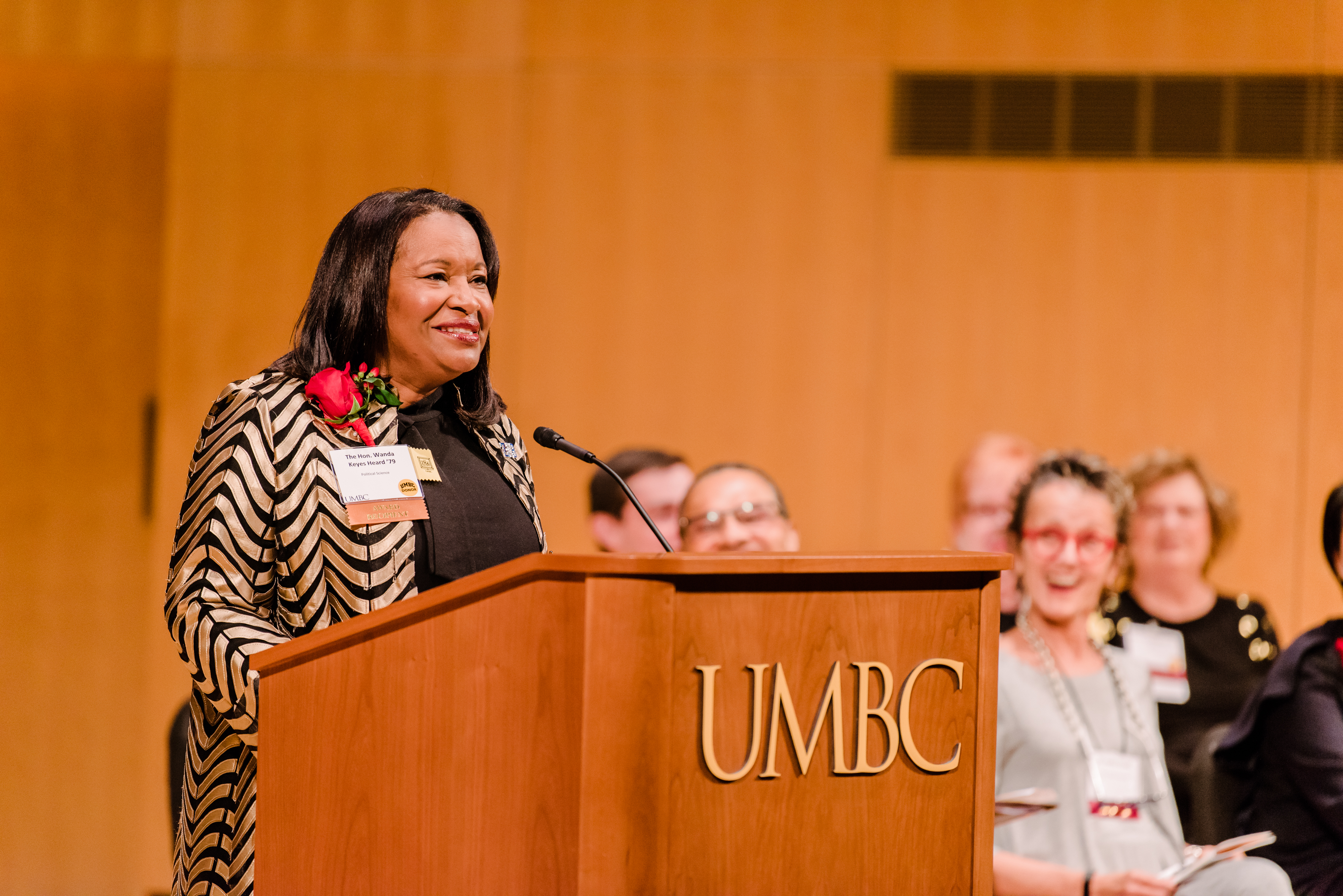 Woman with red flower gives speech at alumni awards