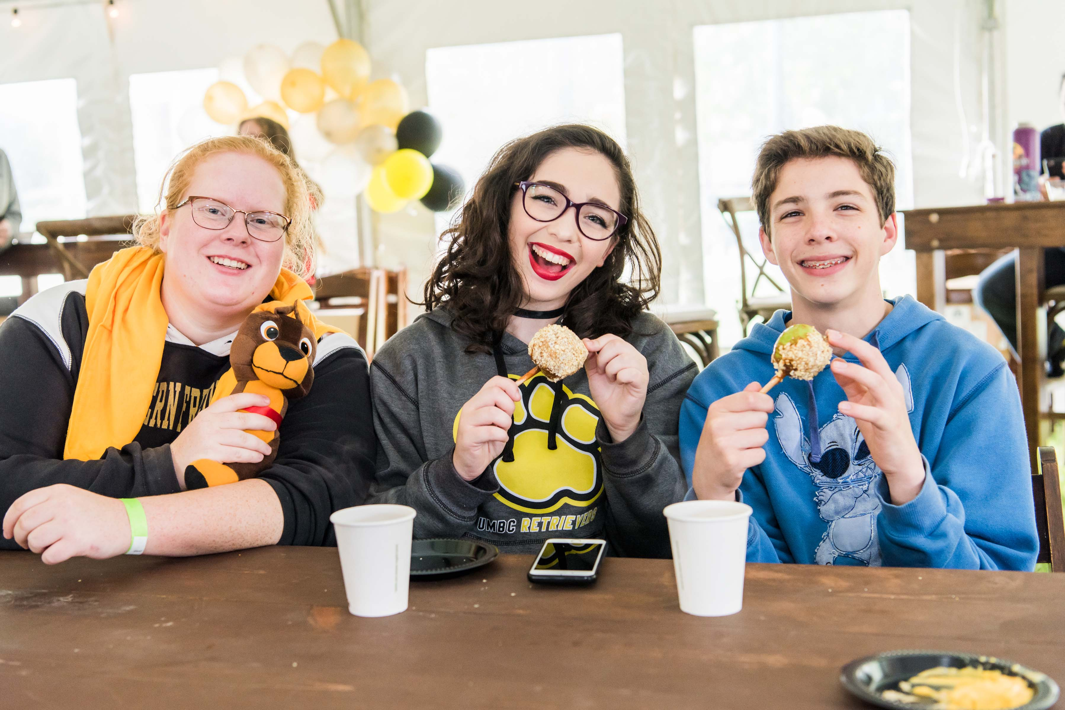 Students pose with tiny candy apples under tent