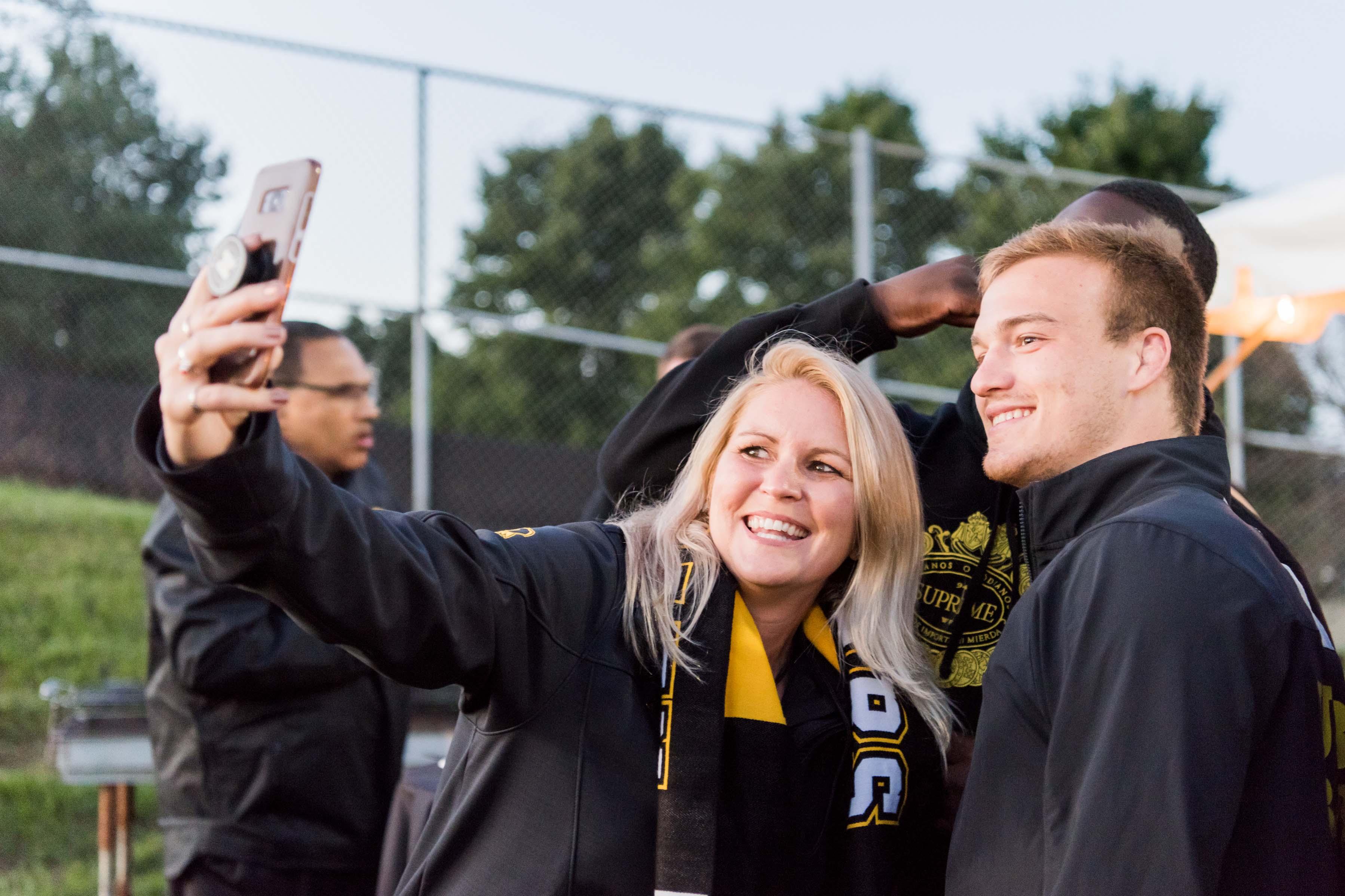 Three people take selfie on soccer field