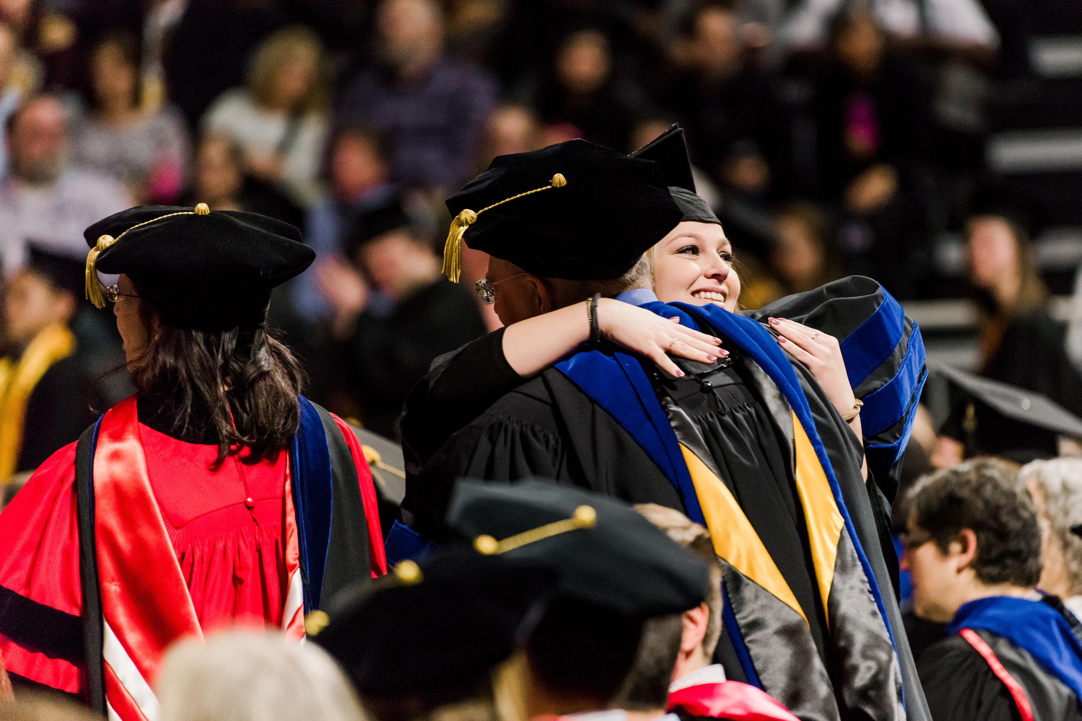 Two people in graduation garbs hugging