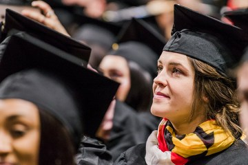 Graduate smiles toward stage maryland flag around her neck