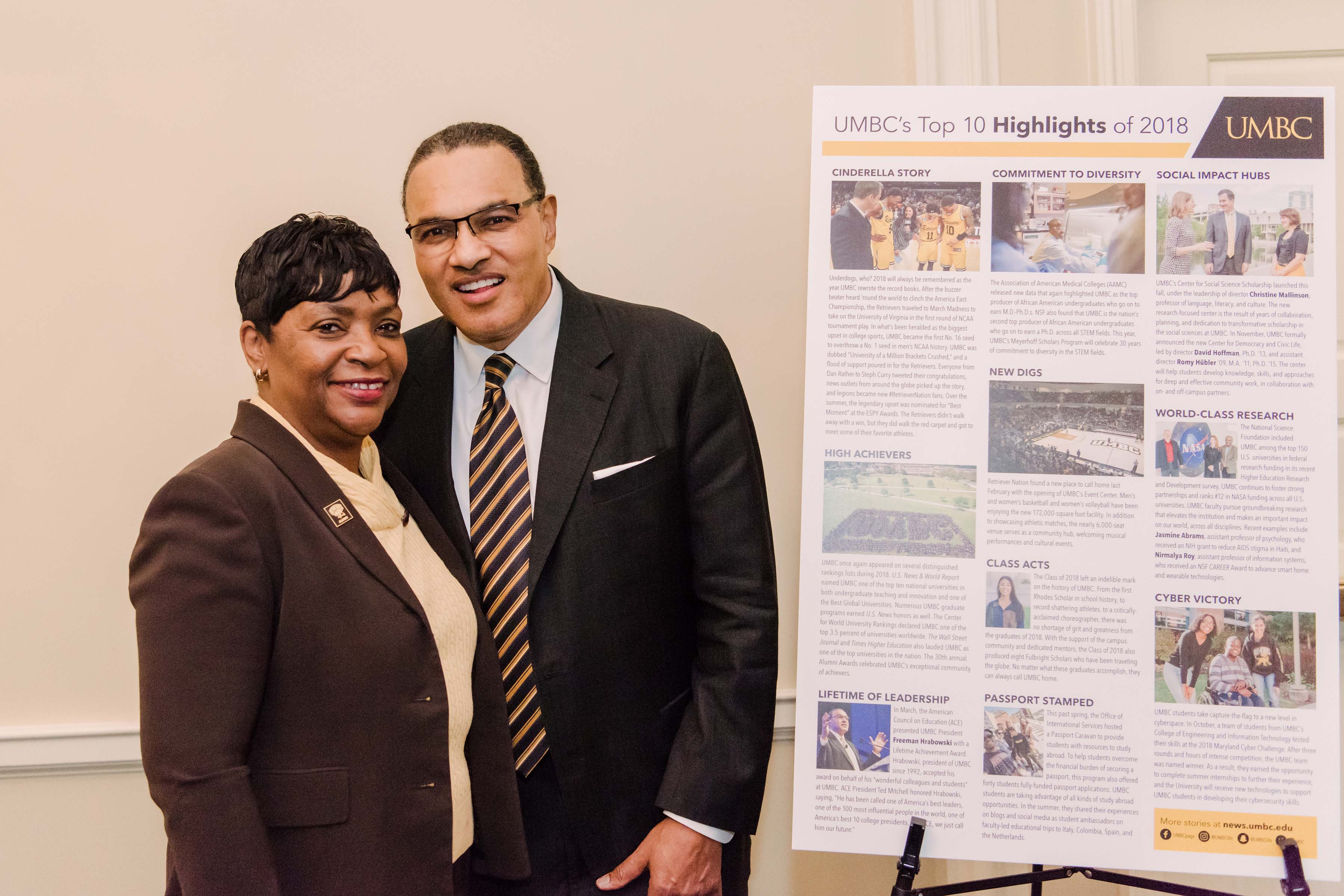 Woman poses with Hrabowski UMBC's top 10 highlights of 2018 sign in background