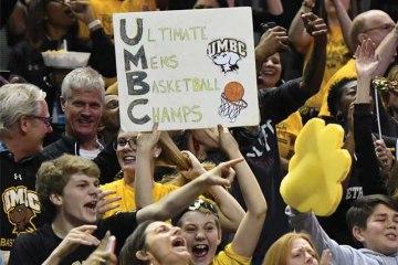 Fan holds ultimate mens basketball champ sign