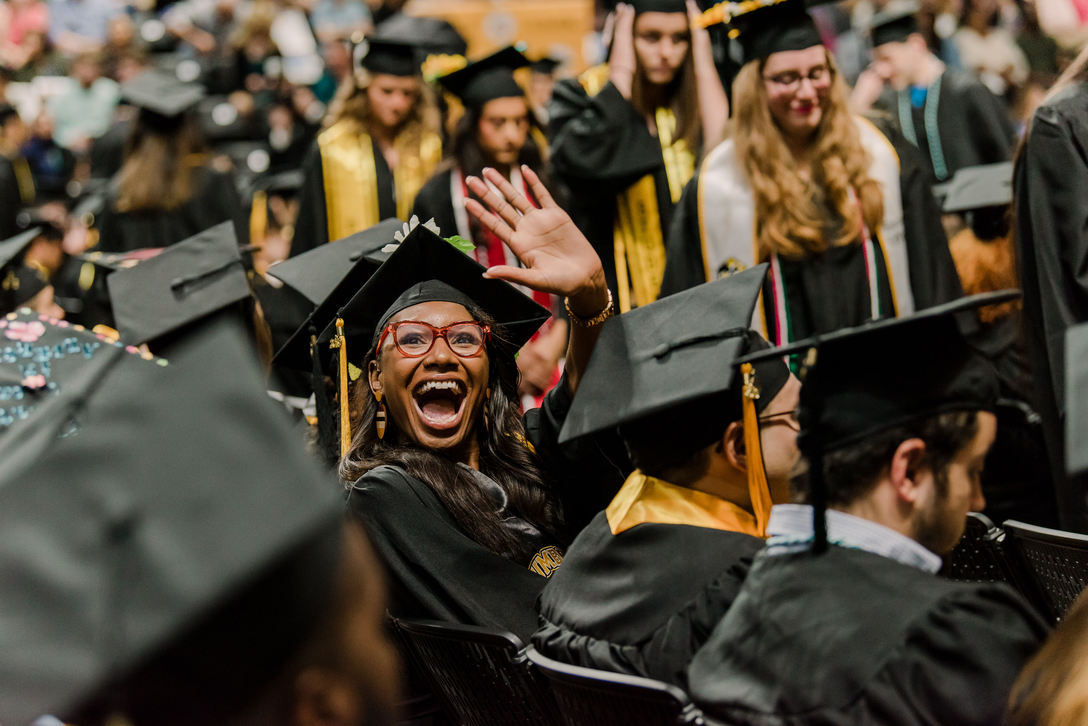 An excited graduate waves to the audience during spring commencement.