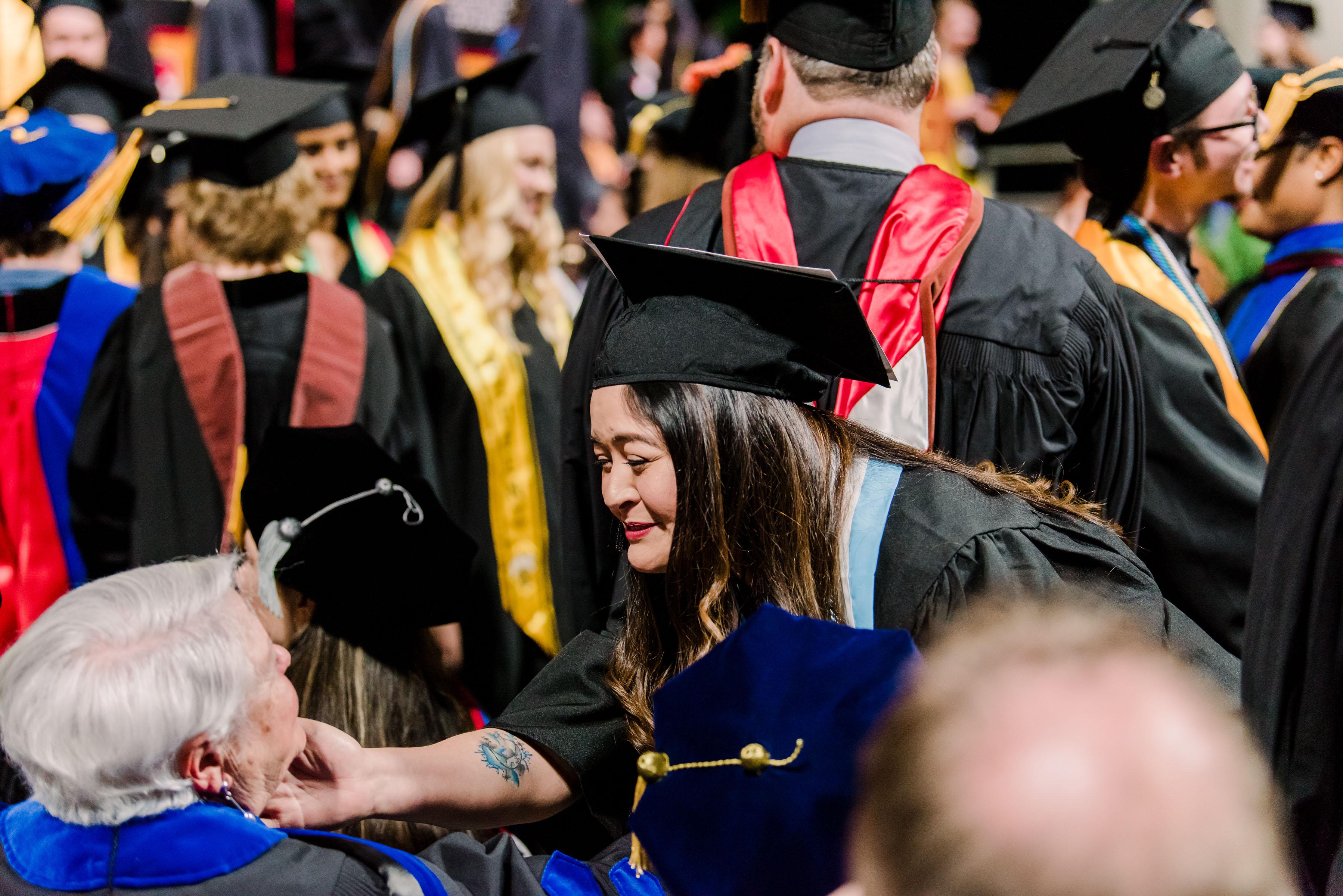 Women reaches to embrace older women at graduation