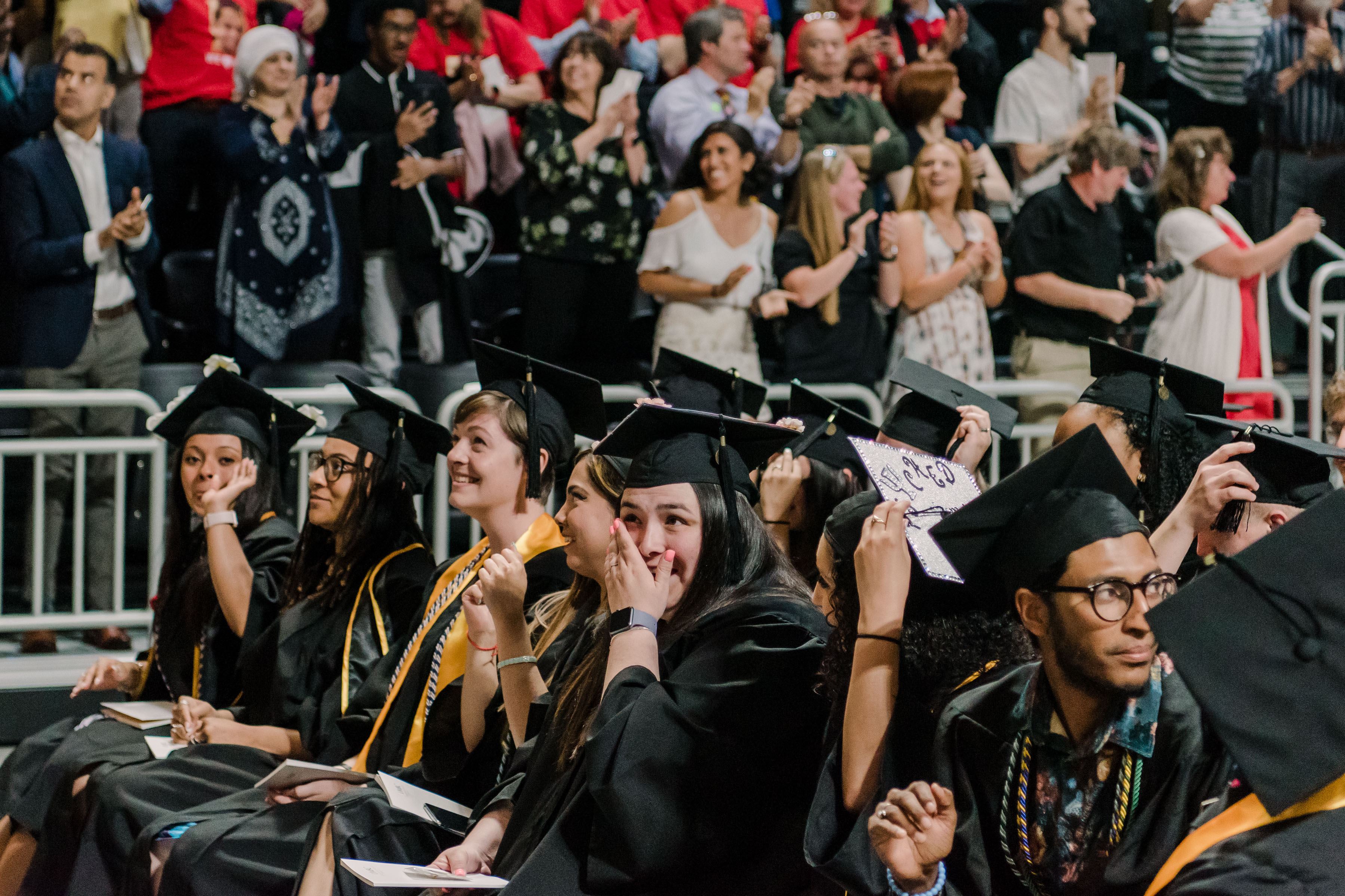 An emotional student wipes away tears during spring commencement 2019