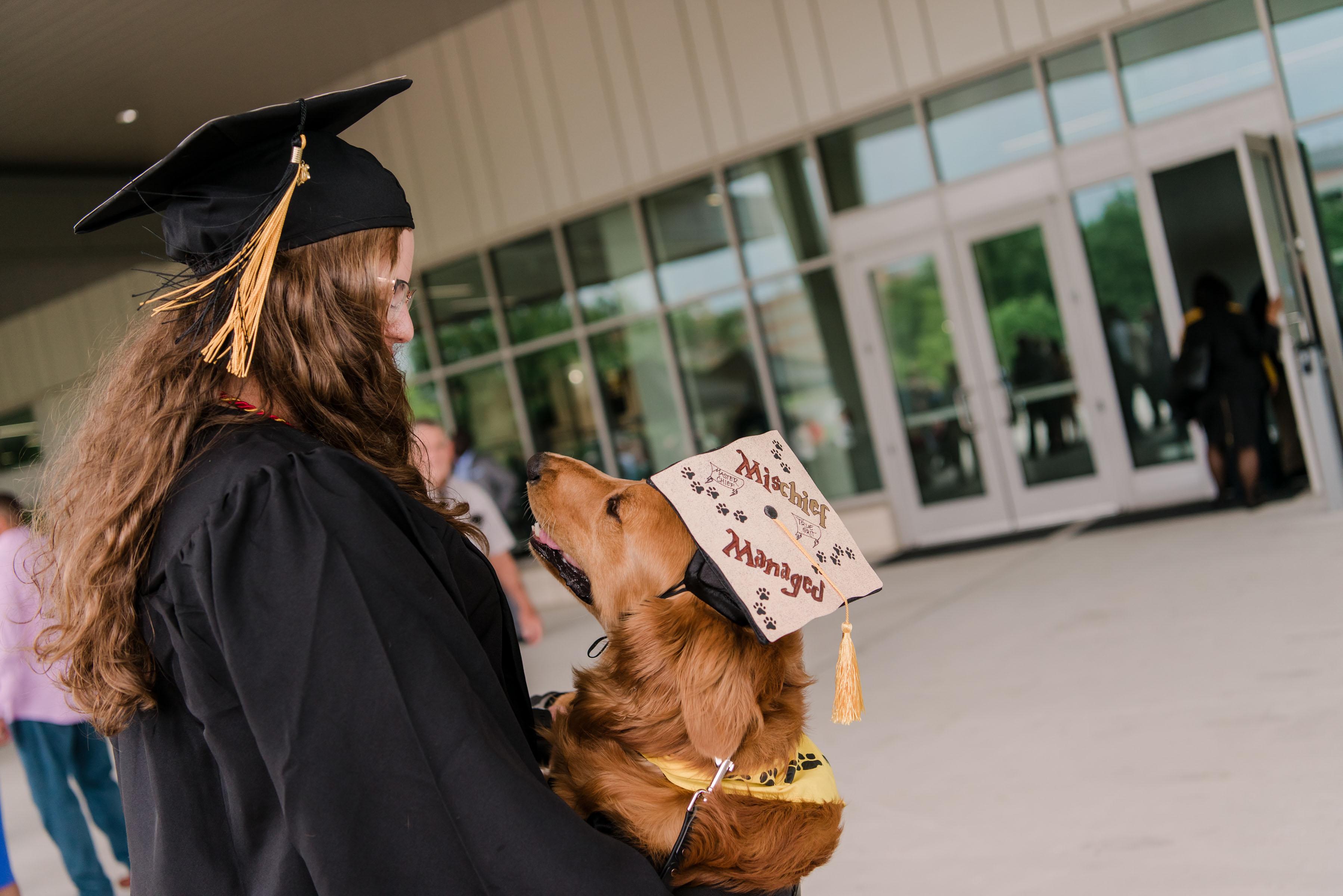 Woman in graduation robes hug dog with graduation cap
