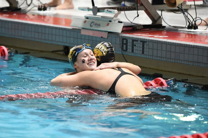 Haylee Committee hugs Tonia Papapertrou after the 100 freestyle. Photo by Colleen Humel.
