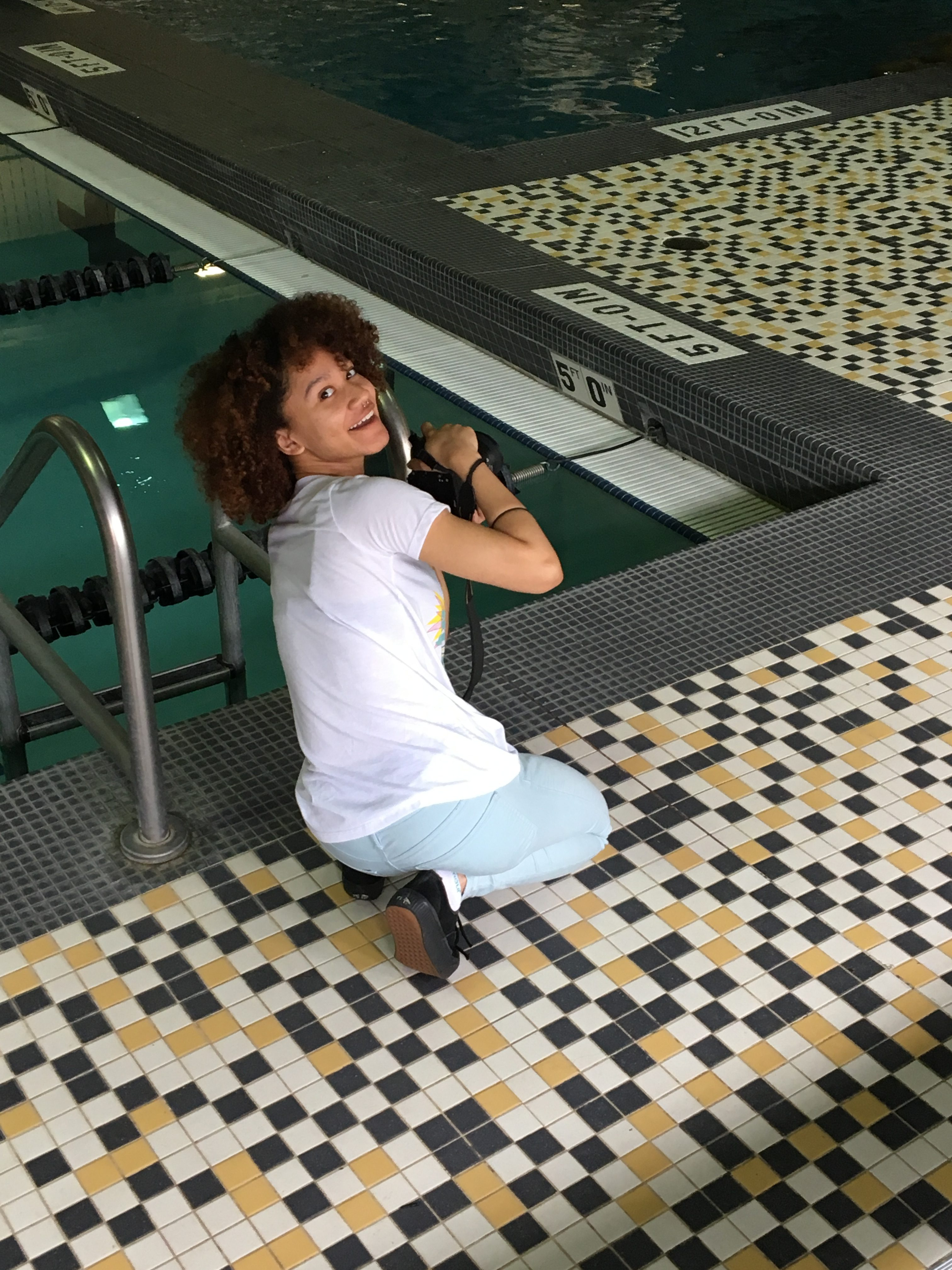 raquel with camera looks at camera from beside pool