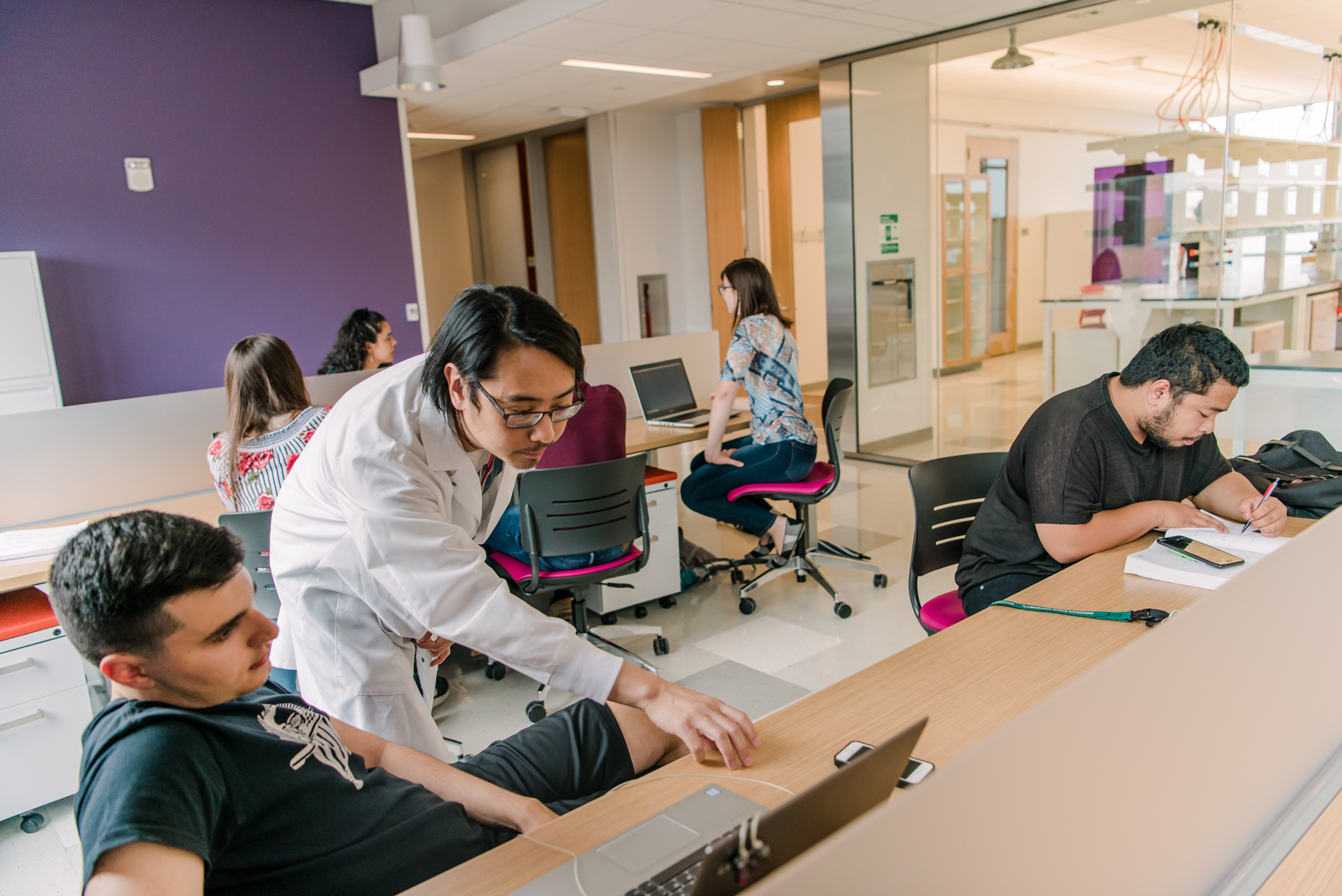 People work at desks in ILSB with student in lab coat helping out