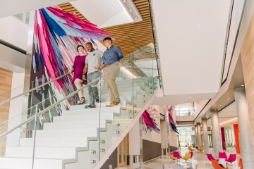 Three people walk down steps in ILSB building