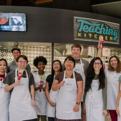 Group of people in aprons smile in Teaching Kitchen
