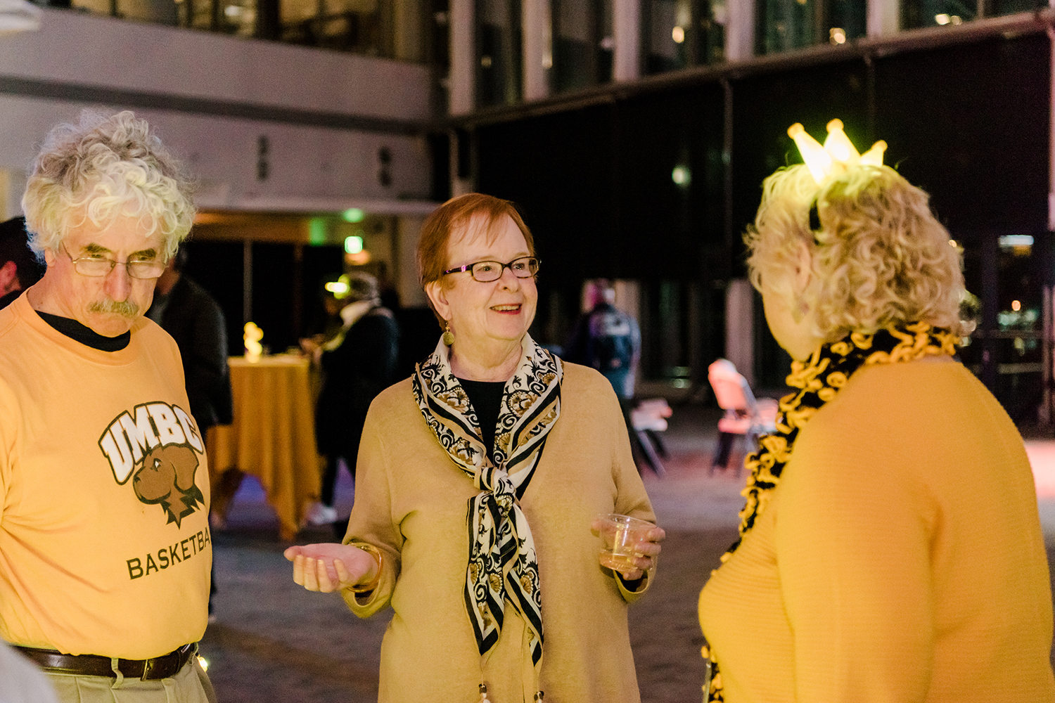Three people in UMBC colors at the Light City UMBC Reception