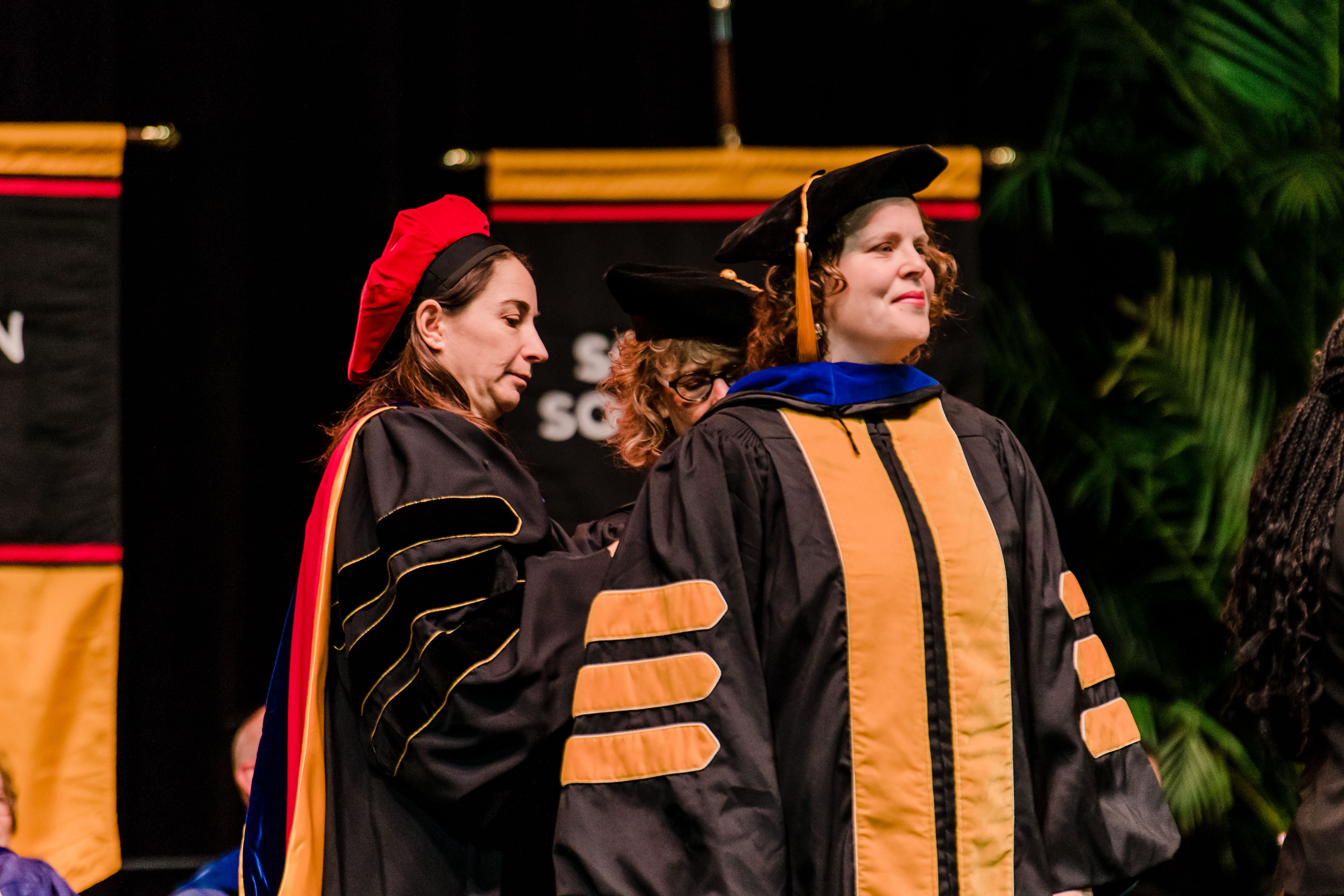 professors in graduation regalia help each other with outfit