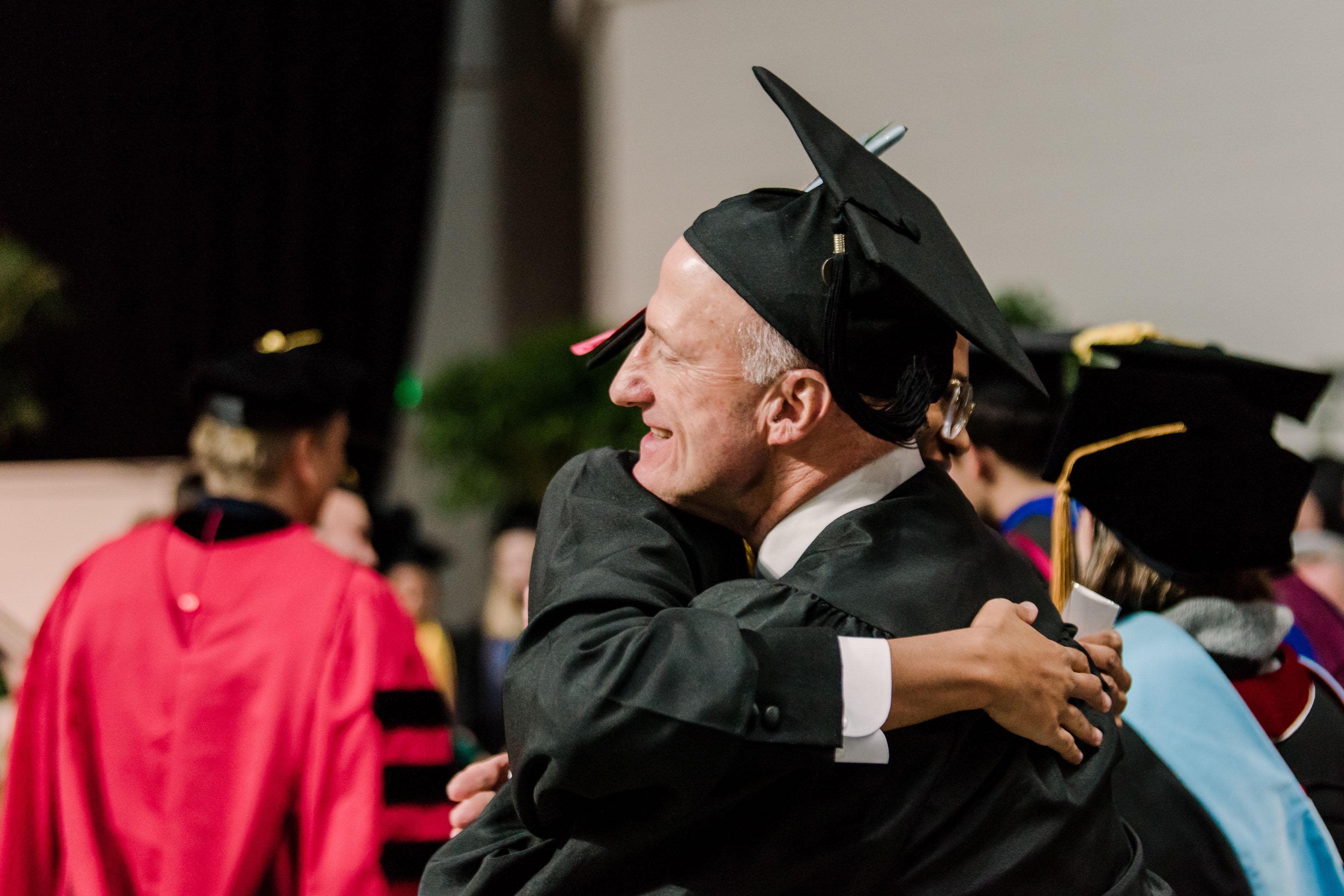 hugging people in graduation garb
