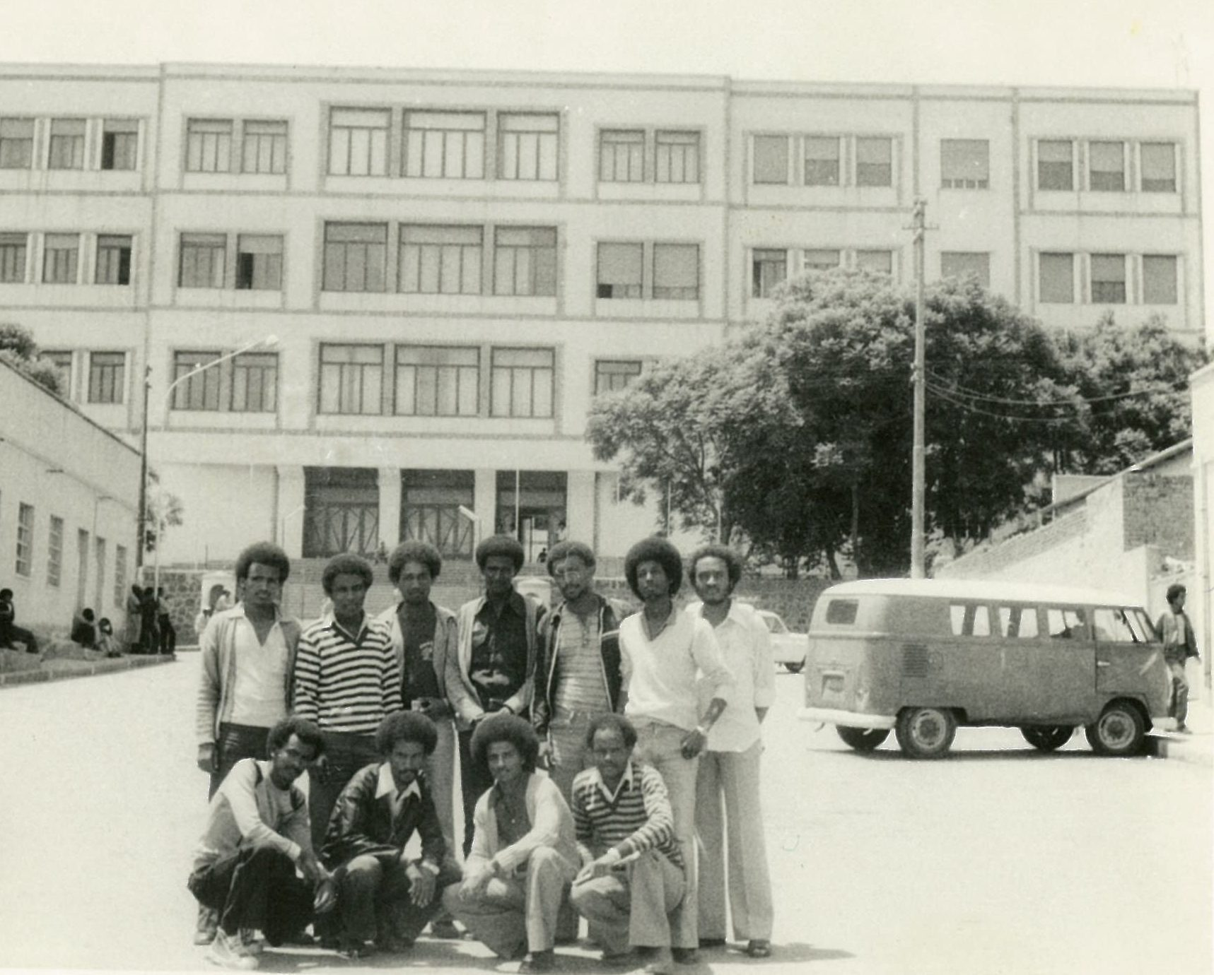 Black and white photo of group of black men posing in front of building
