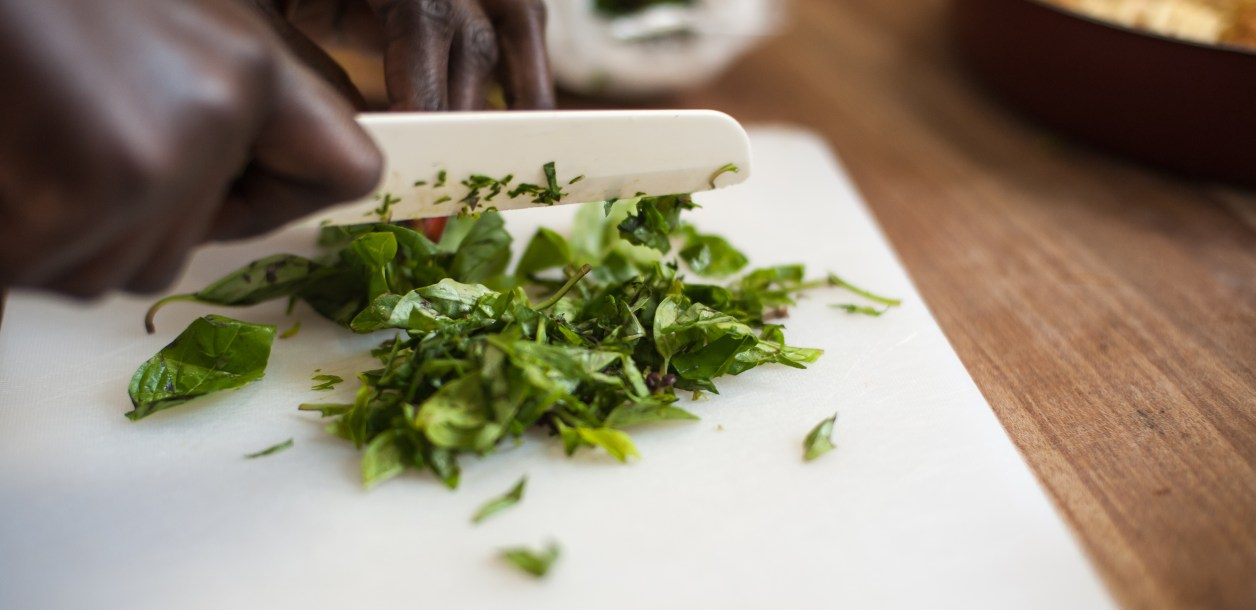 Close-up of a person cutting basil on a white cutting board