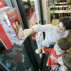 Mother and children take sanitizer wipes from a sanitizing station in Chick-fil-a