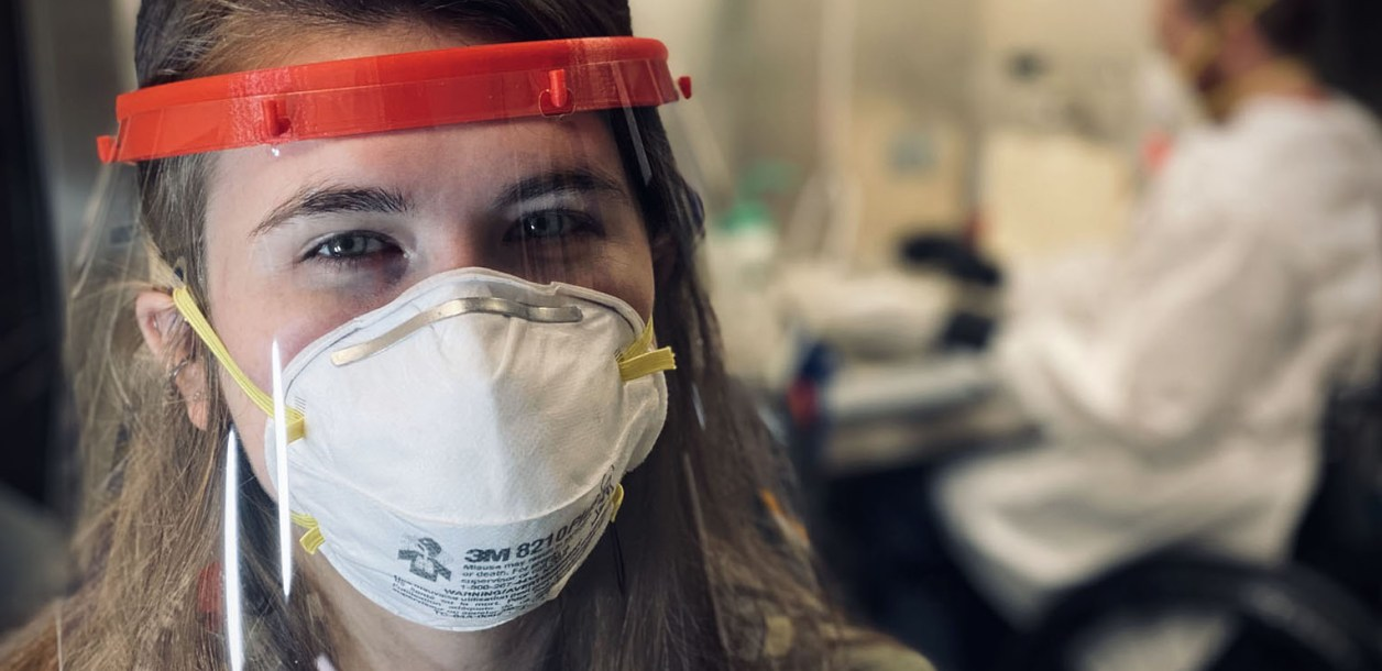 Woman wearing a face shield and mask looks into the camera