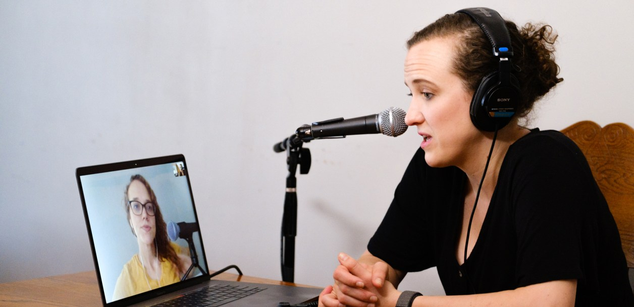 Woman speaks into microphone with another woman on laptop screen