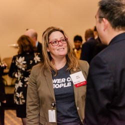 """Nicki Focco, wearing a shirt that reads """"Power of the People,"""" talks with man at a reception"""