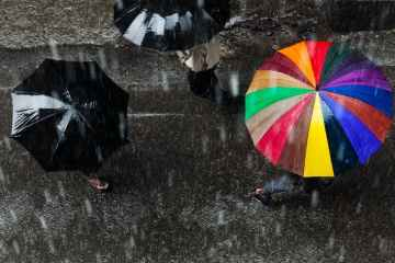 Bird's-eye-view of three people walking in the rain, two with black umbrellas and another with a rainbow umbrella