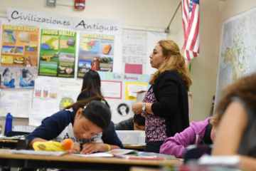 Female teacher walks around classroom decorated in history posters written in Spanish