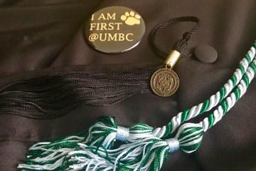 "pin reading ""I am first at UMBC,"" graduation tassel and cord"