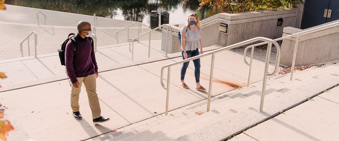 two students walk across campus in masks