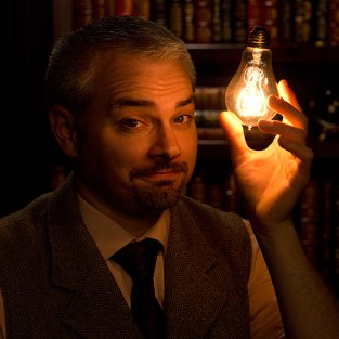 a magician holds a lighted lightbulb