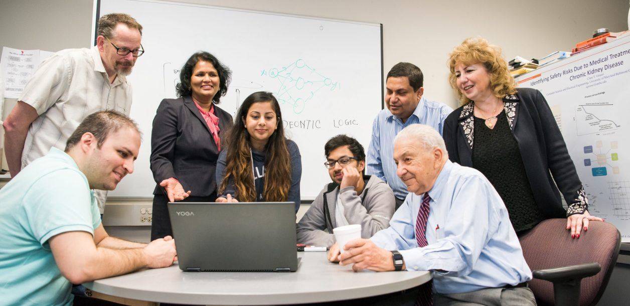 a group of people surround a laptop